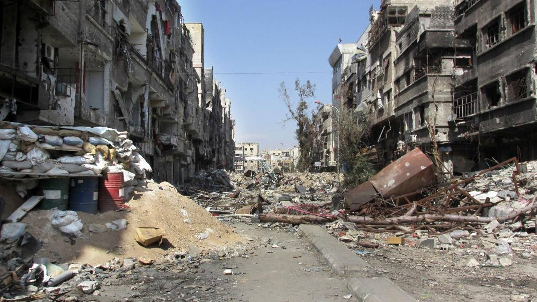 This picture taken on Monday Feb. 24, 2014, and released by the United Nations Relief and Works Agency for Palestine Refugees in the Near East (UNRWA), shows damage and debris on  one of the main streets of the besieged Palestinian camp of Yarmouk, in Damascus, Syria. U.N. Secretary General Ban Ki-Moon urged Syrian government to authorize more humanitarian staff to work inside the country, devastated by its 3-year-old conflict. (AP Photo/UNRWA)
