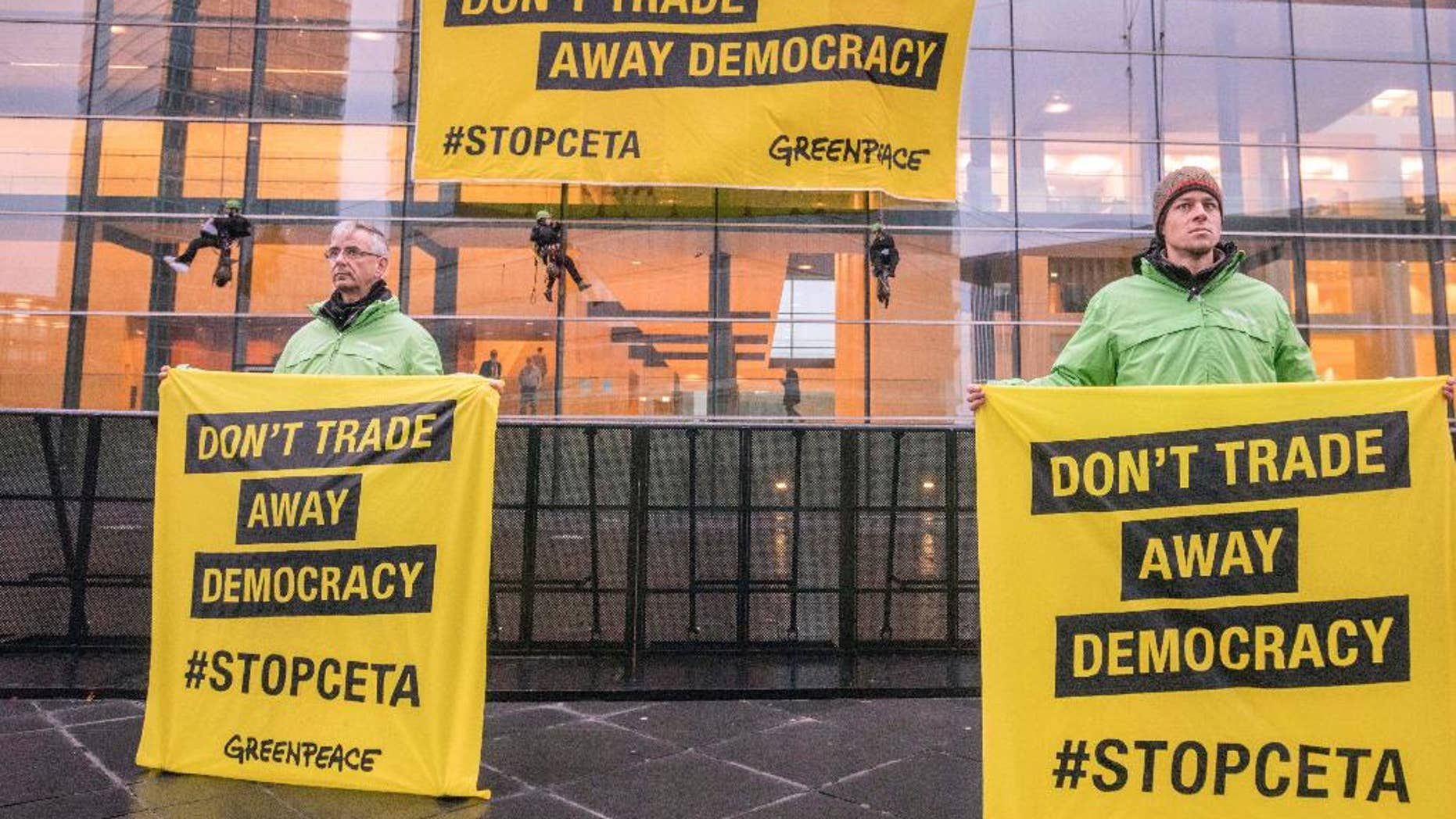 Greenpeace demonstrators hold protest banner outside a meeting venue of EU trade ministers at the EU Council building in Luxembourg, Tuesday, Oct. 18, 2016. European Union trade ministers meet Tuesday to discuss the Comprehensive Economic and Trade Agreement between the EU and Canada. (AP Photo/Olivier Matthys)