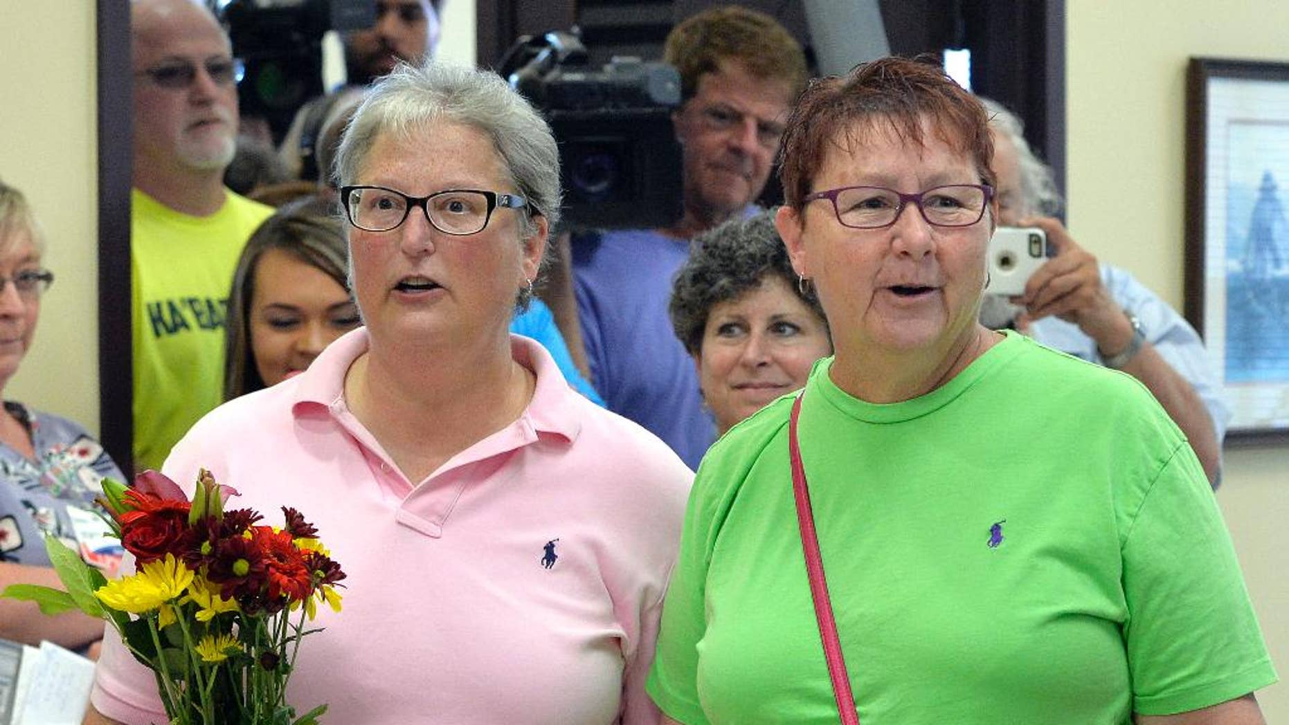 April Miller, left, and her partner Karen Roberts arrive to obtain their marriage license at the Rowan County Judicial Center in Morehead, Ky., Friday, Sept. 4, 2015. Miller, one of the plaintiffs in the suit against Rowan County Clerk Kim Davis, applied for her license with her partner less than 24 hours after Davis was jailed on contempt charges. (AP Photo/Timothy D. Easley)