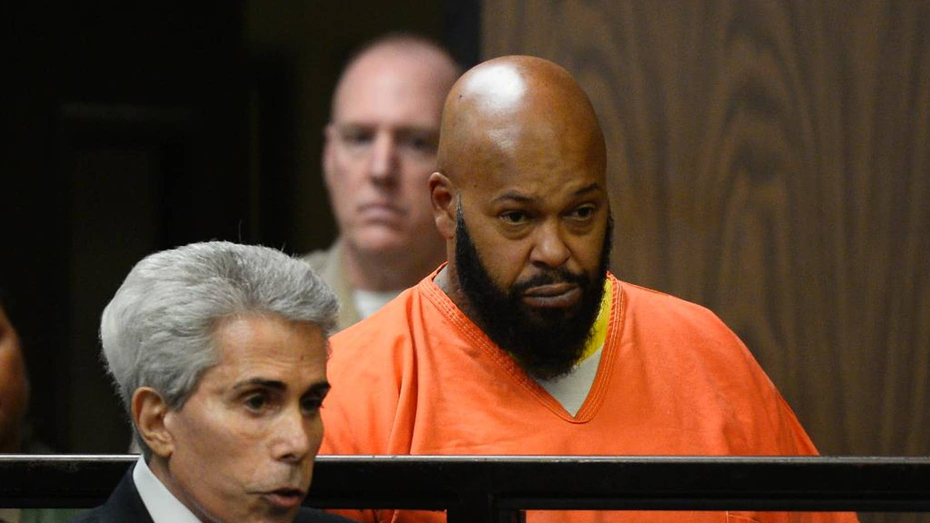 """FILE - In this Tuesday, Feb. 3, 2015, file photo, Marion """"Suge"""" Knight, right, is joined by his attorney David Kenner, left, during his arraignment, in Compton, Calif. Knight's lawyer says a video of a confrontation that ended in a fatal hit-and-run appears to show the former rap mogul was ambushed. Kenner says he has briefly reviewed the video that was obtained from a Compton burger stand of the Jan. 29, 2015 confrontation, which left one man dead and another seriously injured.  (AP Photo/Paul Buck, Pool, File)"""