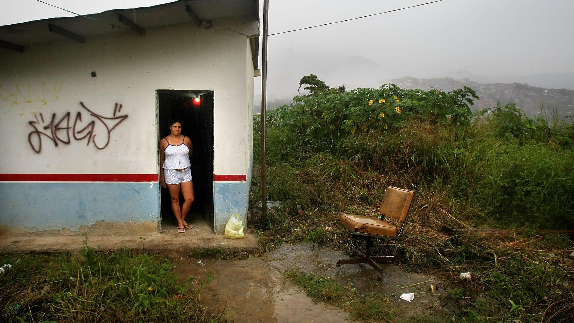 Carolina Olivera stands in her front door in the poor barrio of Petare in Caracas, Venezuela.
