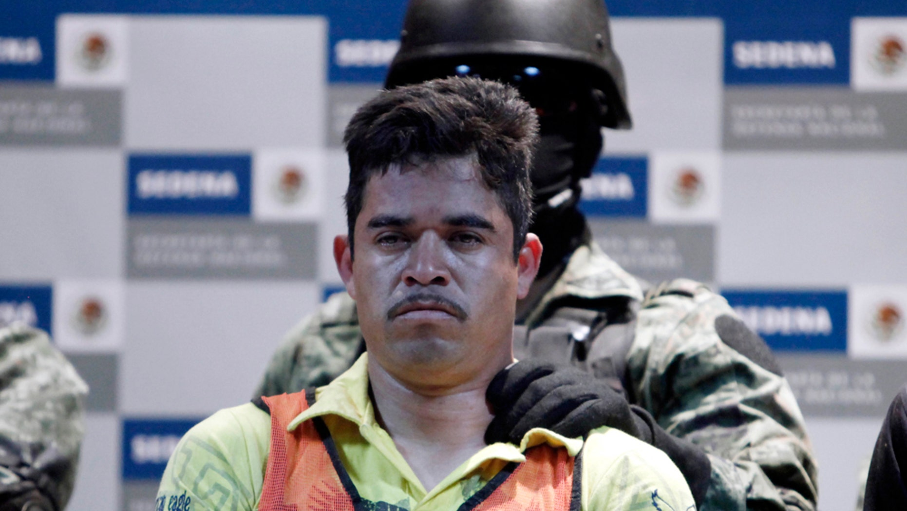 """A soldier escorts Julian Zapata Espinosa, aka """"El Piolin"""", alleged member of the Los Zetas drug cartel and main suspect in the killing of U.S. Immigration and Customs, ICE, agent Jaime Zapata, during a presentation for the media in Mexico City, Wednesday, Feb. 23, 2011. Zapata and fellow agent Victor Avila, were attacked Feb. 15 when traveling along a highway in Mexico's San Luis Potosi state. Avila survived the attack. (AP Photo/Miguel Tovar)"""