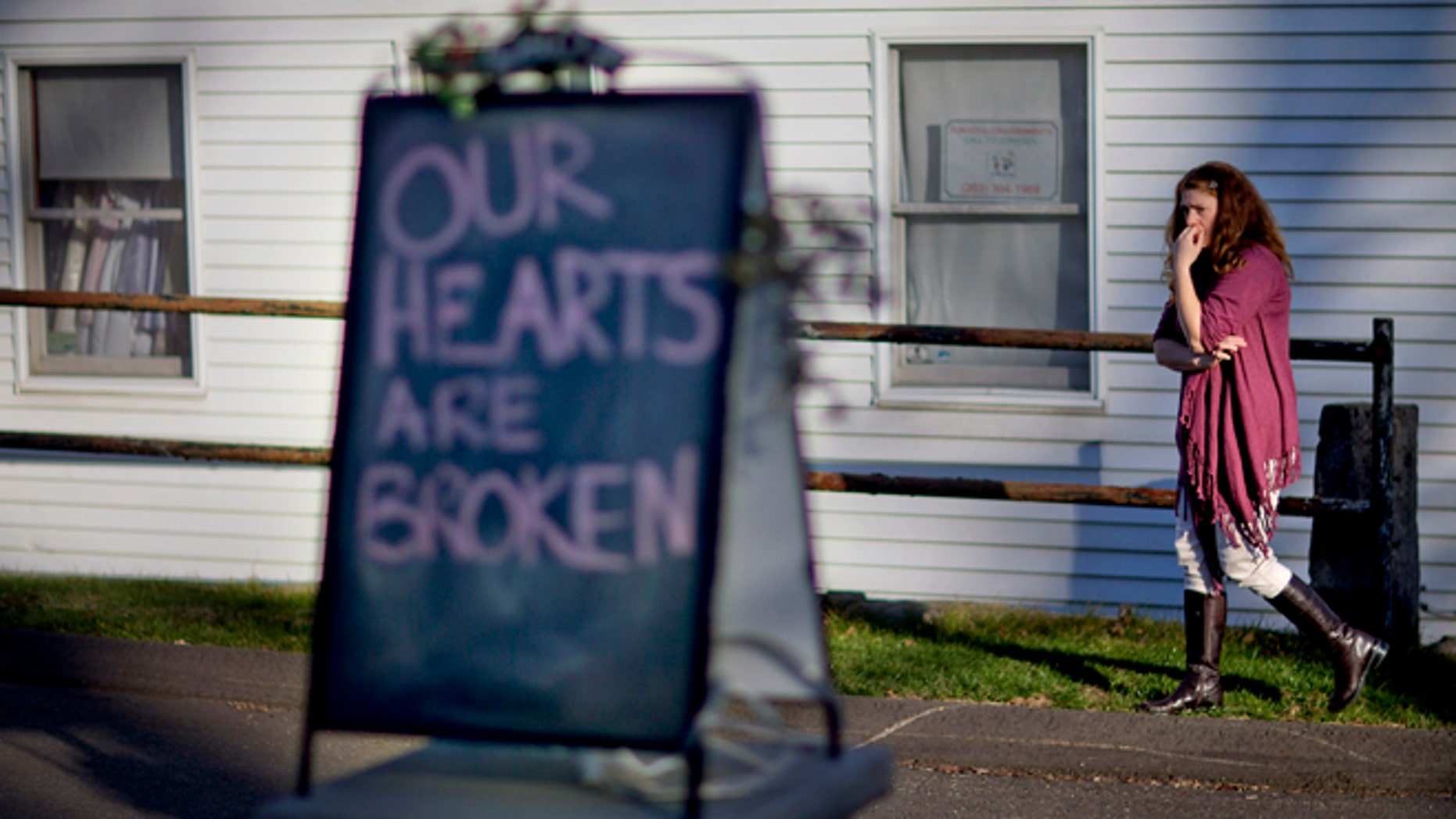 Shop owner Tamara Doherty, paces outside her store just down the road from Sandy Hook Elementary School, Saturday, Dec. 15, 2012, in Newtown, Conn. The massacre of 26 children and adults at Sandy Hook Elementary school elicited horror and soul-searching around the world even as it raised more basic questions about why the gunman, 20-year-old Adam Lanza, would have been driven to such a crime and how he chose his victims. (AP Photo/David Goldman)