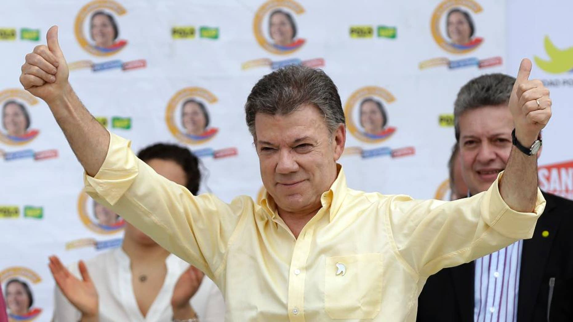 FILE - In this June 5, 2014 file photo, Colombia's President Juan Manuel Santos gives a thumbs up during a campaign event in Bogota, Colombia. A corruption scandal that has spread across Latin America is inching closer to Santos amid new evidence on Monday, March 6, 2017 that suggests a Brazilian construction company paid $1 million for an opinion poll carried out during his re-election campaign. (AP Photo/Fernando Vergara, File)