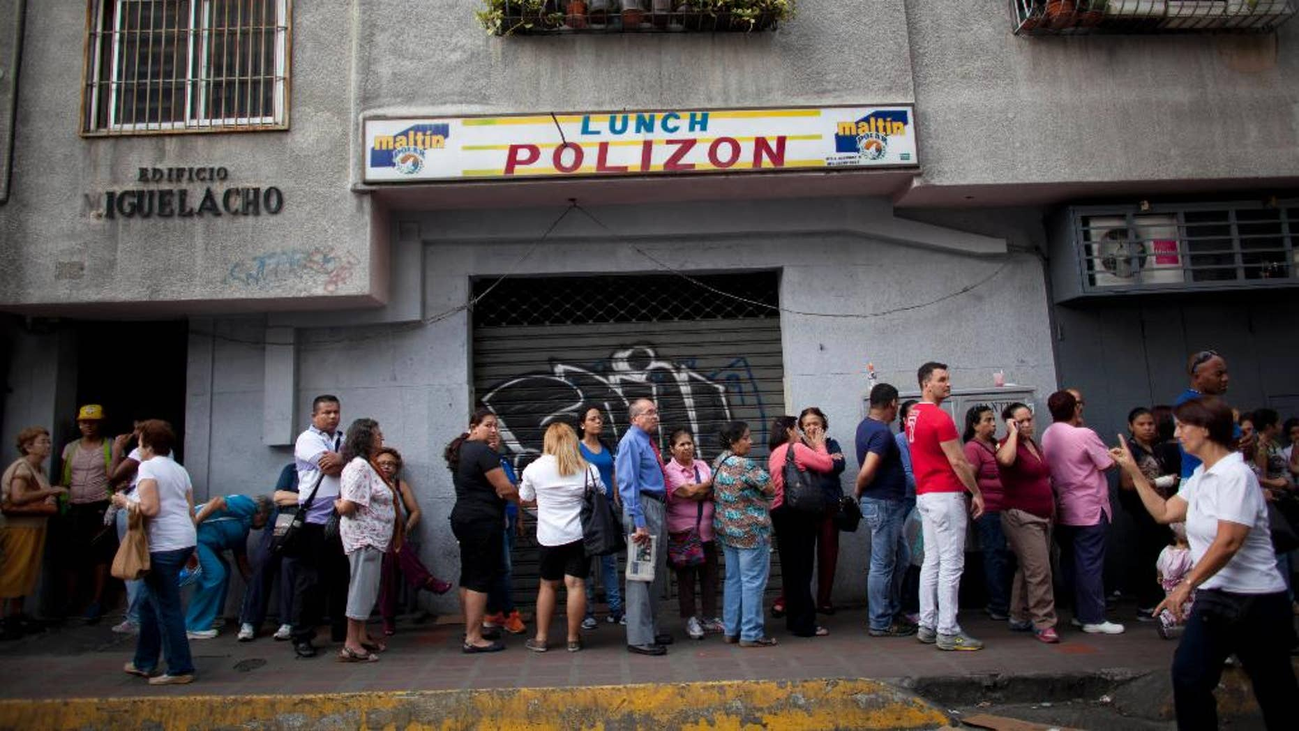 FILE - In this Oct. 23, 2014 file photo, people wait in line to enter a small market to try to buy hard to find items like disposable diapers, laundry detergent and razors in downtown Caracas, Venezuela. President Nicolas Maduro announced Friday, Oct. 31 he is deploying hundreds of inspectors to enforce the government's price regulations on retailers. (AP Photo/Ariana Cubillos, File)