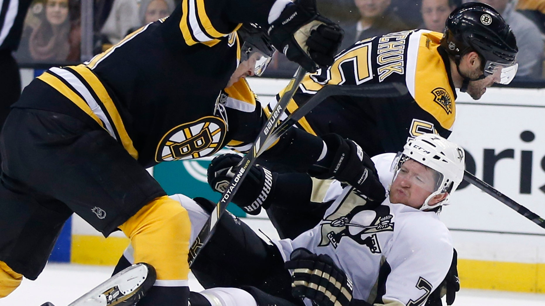 Pittsburgh Penguins defenseman Paul Martin (7) is knocked down by Boston Bruins defensemen Matt Bartkowski, left, and Johnny Boychuk (55) in the third period of an NHL hockey game in Boston, Monday, Nov. 25, 2013. The Bruins won 4-3 in overtime. (AP Photo/Elise Amendola)