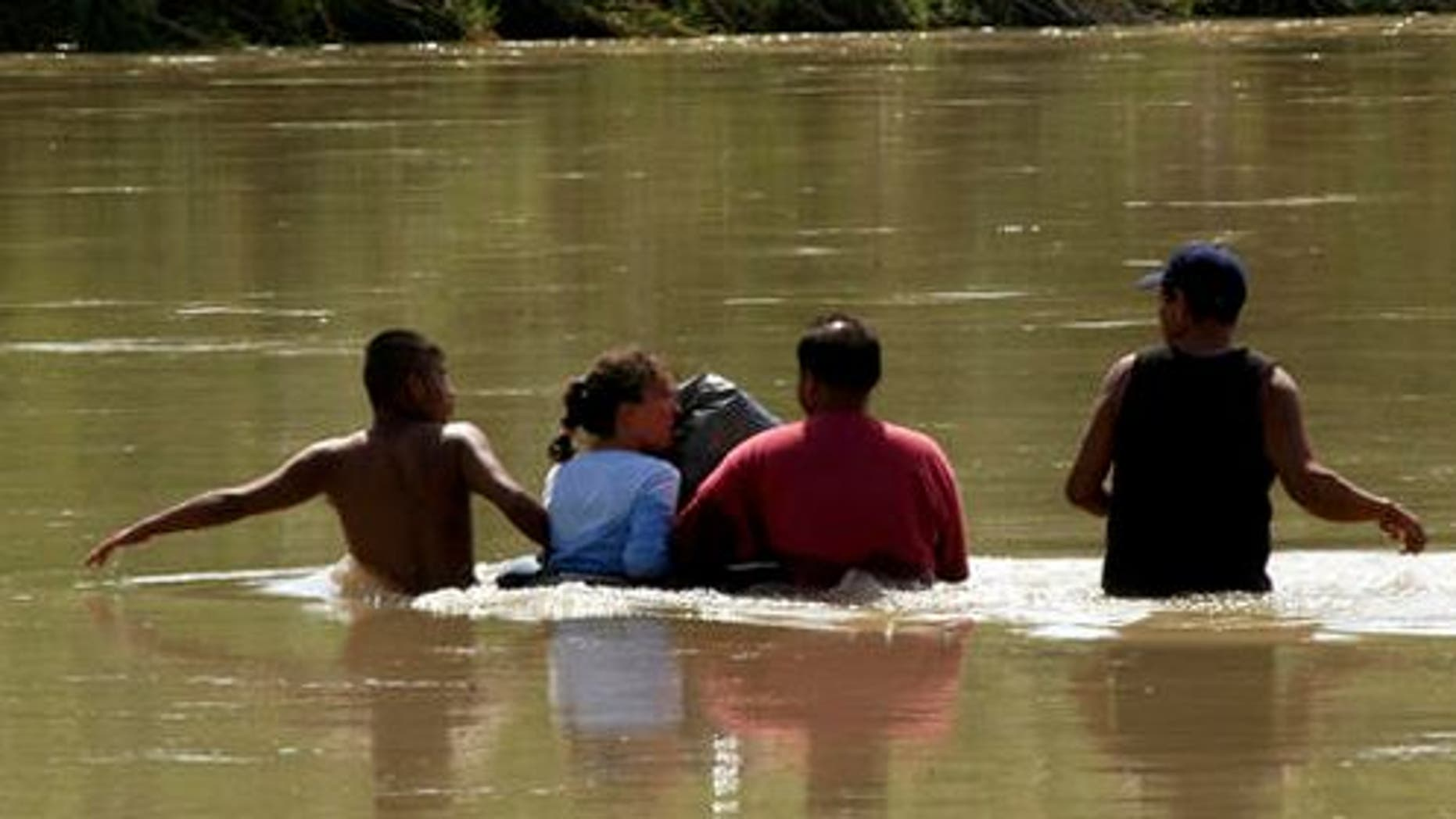 "Unidentified migrants, who did not wish to give their names, from the state of Jalisco, Mexico, cross the waters of the Rio Grande, with the help of two ""coyotes"" or  smugglers, in an attempt to reach the U.S. border, in Nuevo Laredo, Mexico on Wednesday, May 18, 2006. Migrants preparing to cross the border in Nuevo Laredo said they would prefer to climb walls than make dangerous trips through the desert into Arizona and New Mexico, routes that have become popular after U.S. authorities made it tougher to cross near San Diego and El Paso, Texas.   (AP Photo/German Garcia)"