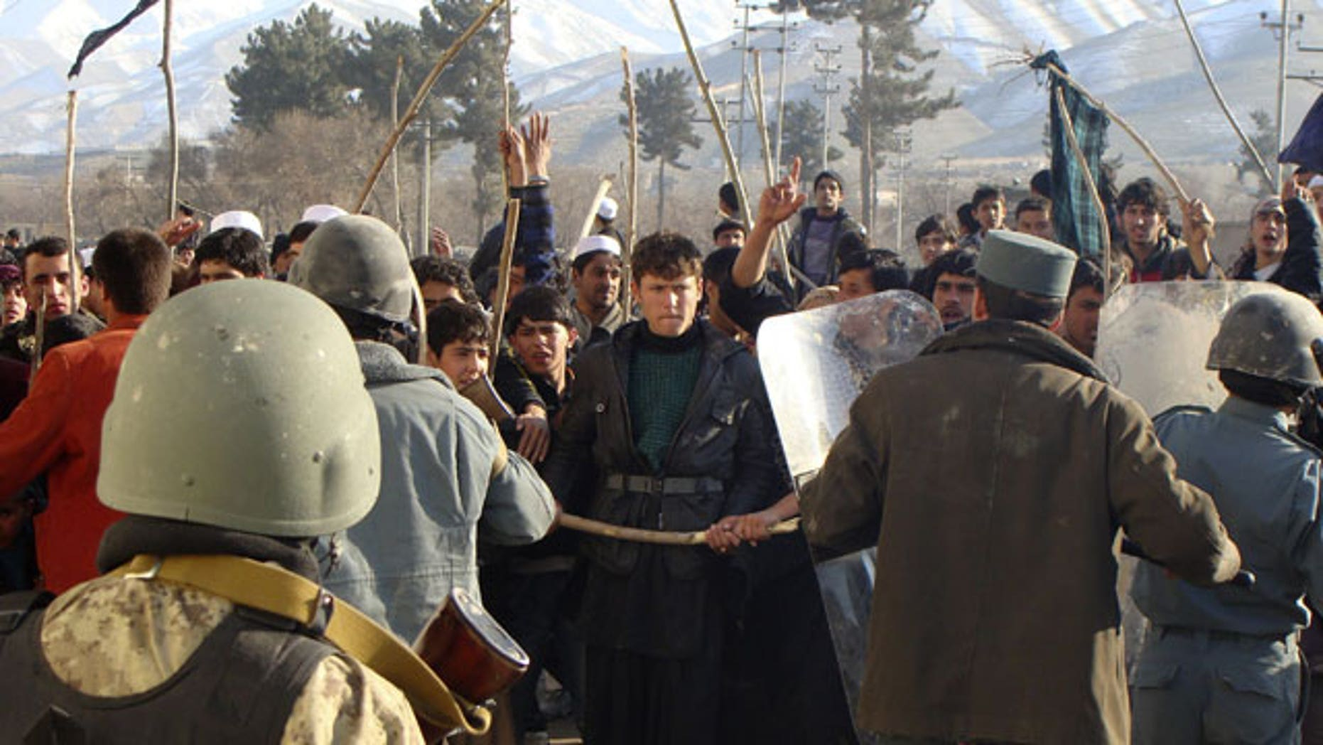 Feb. 24, 2012: Afghan police tries to restrain demonstrators during an anti-US protest in Baghlan province, north of Kabul, Afghanistan.