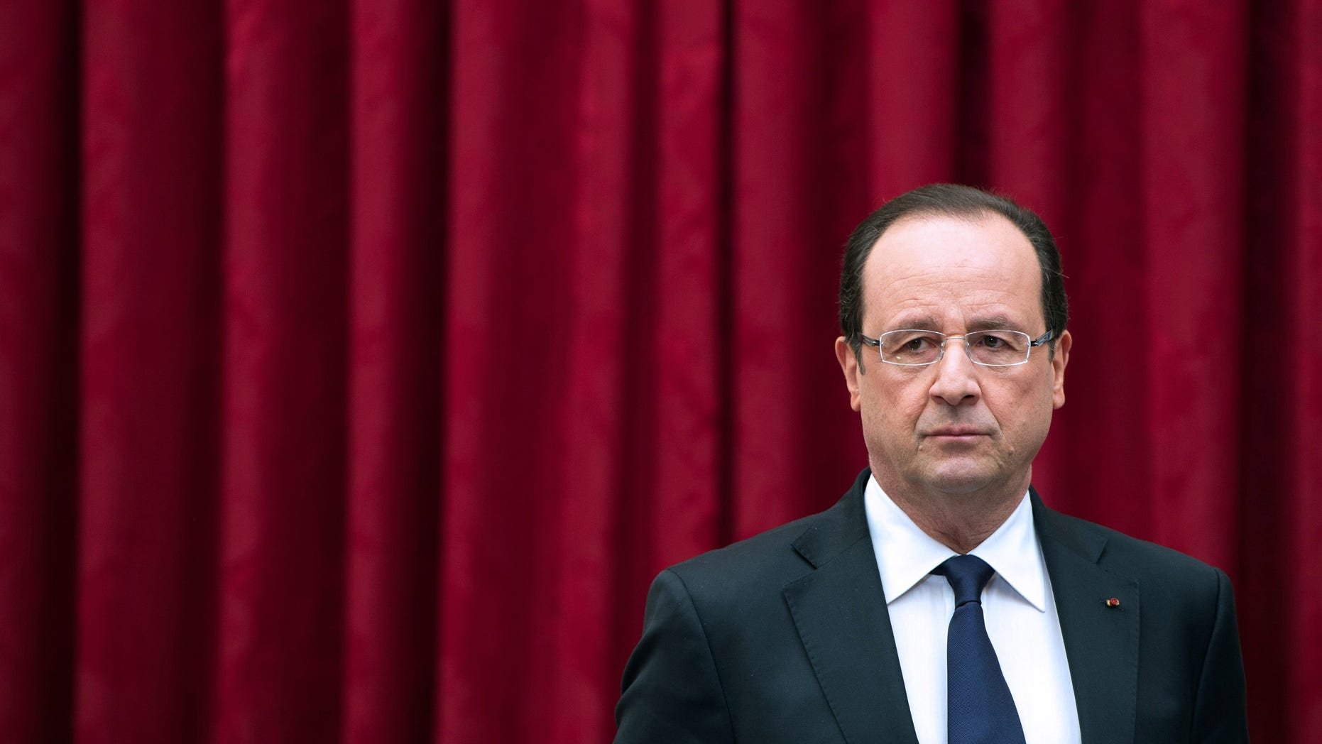 France's President Francois Hollande arrives to deliver a speech to ministers and members of the White Book of Defense and National Security committee at the Elysee presidential palace in Paris, Monday April 29, 2013. France said Monday it will cut another 24,000 military jobs by 2019 as it attempts to maintain a force ready to deal with global threats at the time when the bill for France's decades of deficit spending is due. (AP Photo/Bertrand Langlois, Pool)