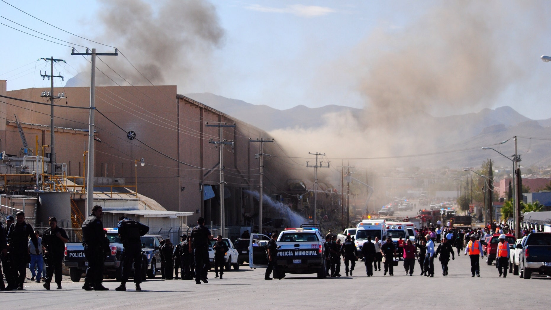 Police and rescue workers gather at a candy factory after an explosion in Ciudad Juarez, Mexico, Thursday, Oct. 24, 2013.  The explosion happened at the Dulces Blueberry factory and caused the floor to collapse, said factory worker Ismael Bouchet. (AP Photo/Raymundo Ruiz)