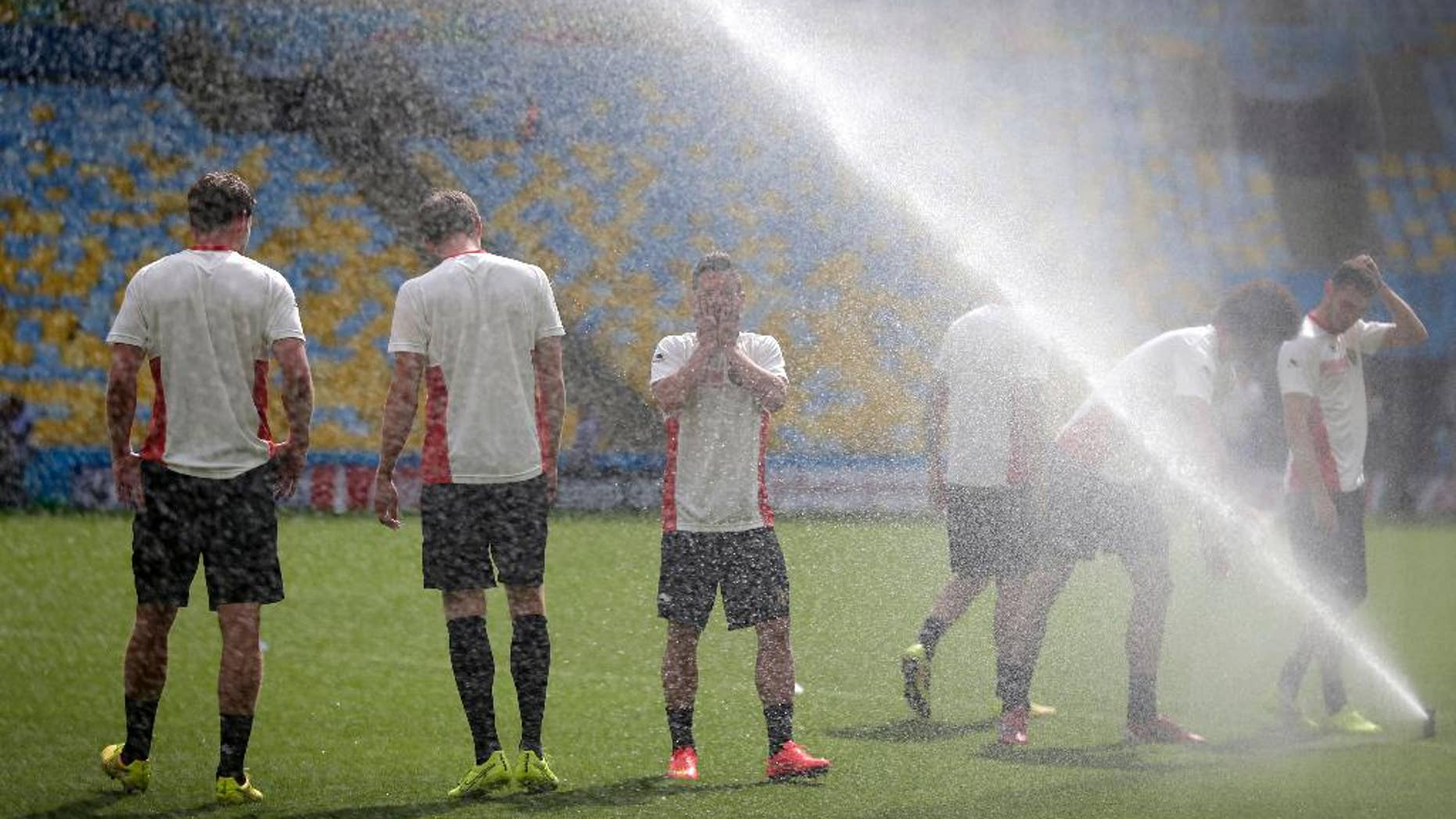 Steven Defour, center, of the Belgium soccer team wipes his face from the spray of a sprinkler at a training session at the Maracana Stadium in Rio de Janeiro, Brazil, Saturday, June 21, 2014. Belgium play in group H of the 2014 soccer World Cup.(AP Photo/Wong Maye-E)