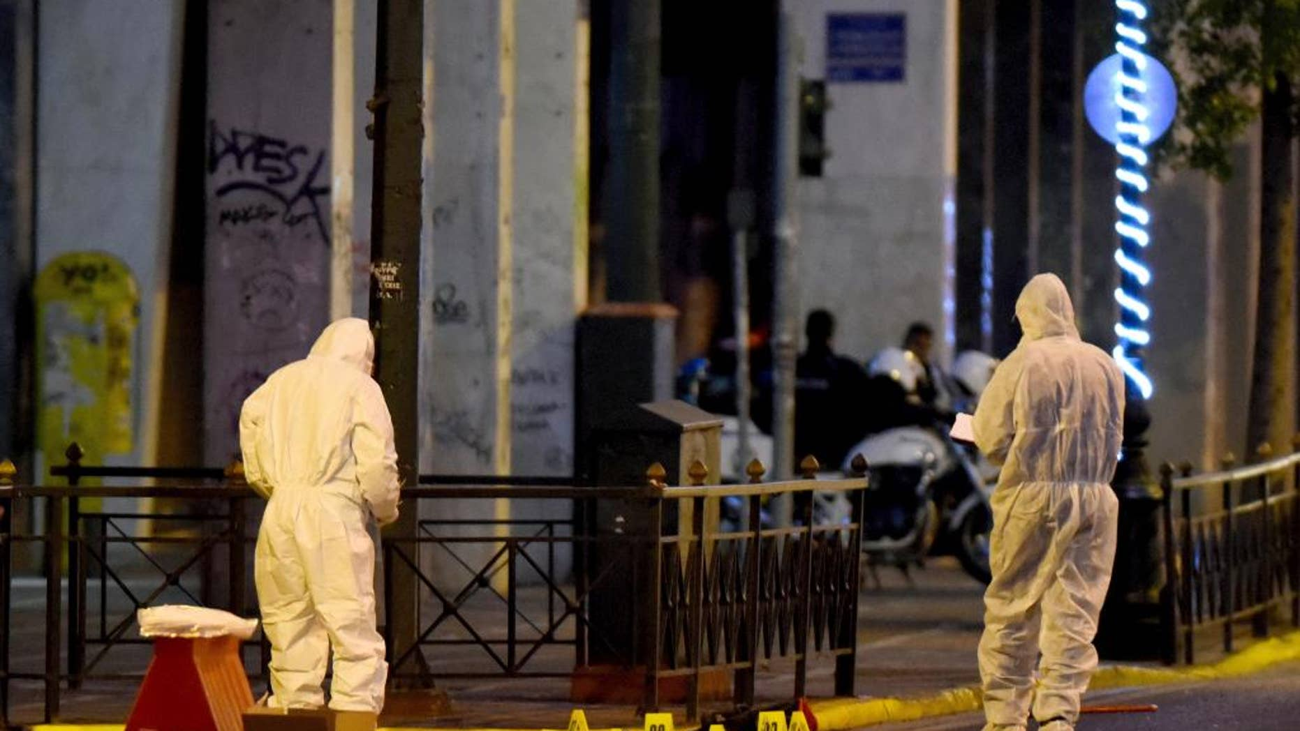 Members of the bomb squad search for evidence outside Labor Ministry in Athens early Monday, Dec. 12, 2016. Greek authorities have destroyed a time bomb planted overnight outside the Labor Ministry on a major thoroughfare in central Athens, after a warning telephone call was made to a newspaper, police said Monday. No injuries or damage were reported. (Antonis Nikolopoulos/Eurokinissi via AP)