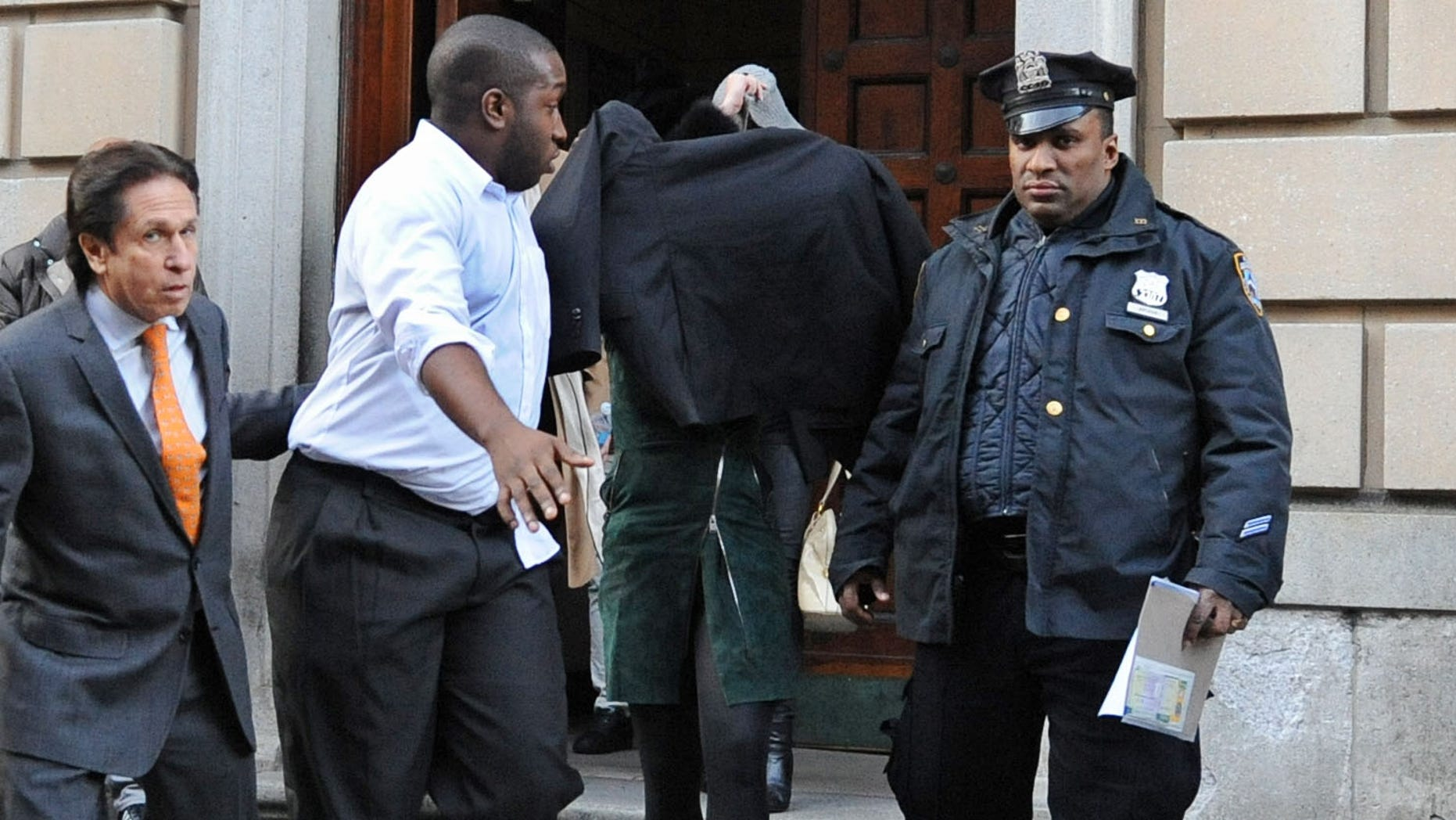 Nov. 29, 2012: Lindsay Lohan, second from right, is escorted from the 10th Precinct police station, with her face shielded in New York after being charged for allegedly striking a woman at a nightclub.
