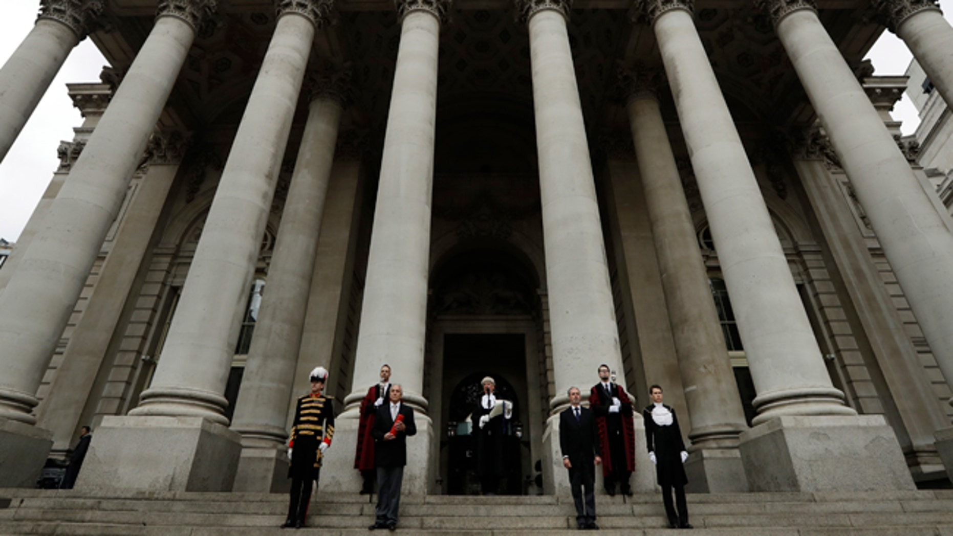 In keeping with traditional practice, Colonel Geoffrey Godbold, center, the City of London Corporation's Common Cryer and Serjeant-at-Arms reads out the Proclamation of the Summons for a new Parliament on the steps of the Royal Exchange, in the City of London, Thursday, May 4, 2017. All 650 seats in the House of Commons are up for grabs in the June 8 election. (AP Photo/Matt Dunham)
