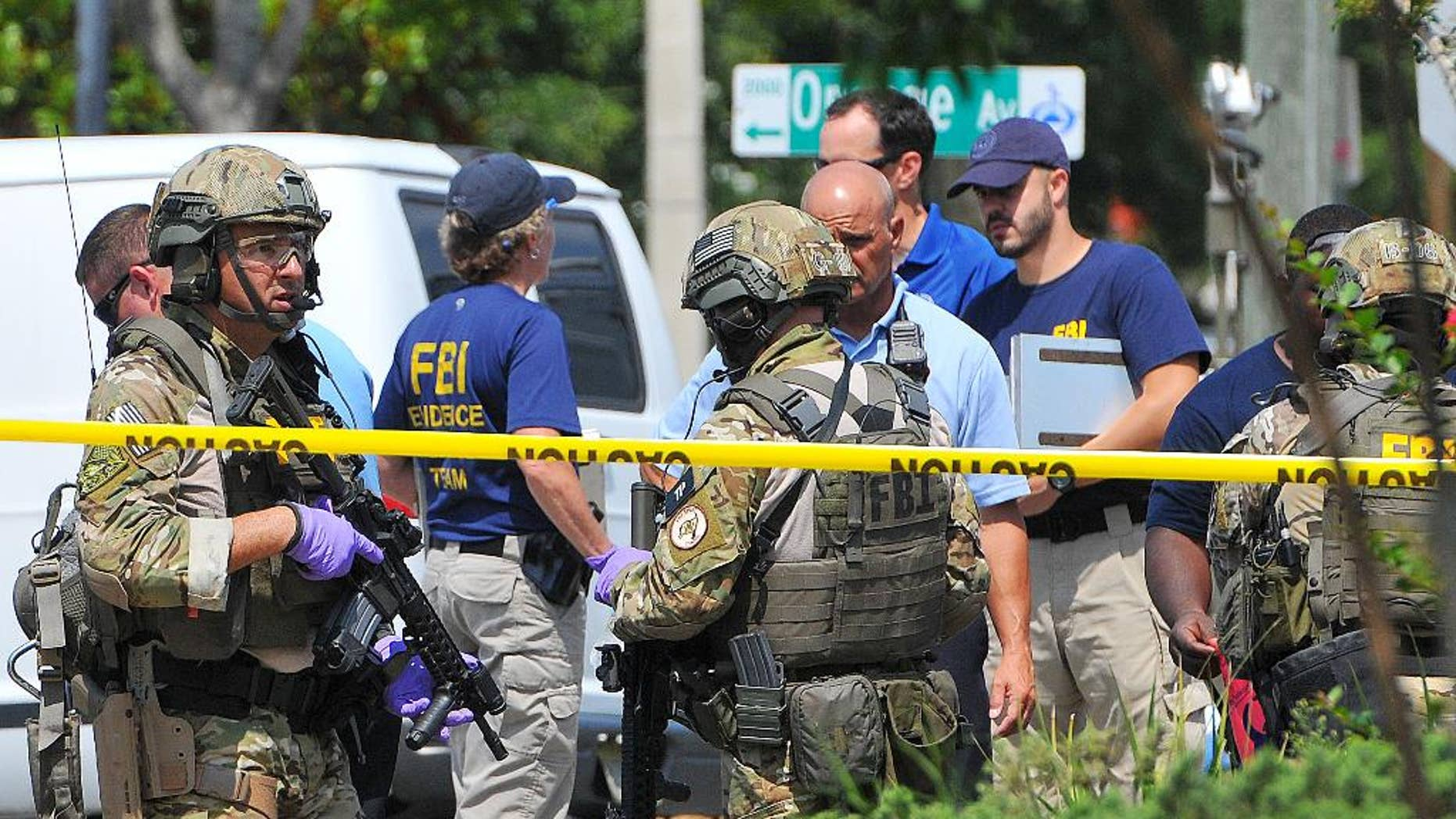 """FILE - In this June 12, 2016 file photo, FBI, Orlando Police Department and personnel from the Orange County Sheriff's Office investigate the attack at the Pulse nightclub in Orlando, Fla. New reports show that law enforcement officials immediately suspected terrorism and adjusted their staging areas due to fears about an explosive device as they responded to reports of shots fired at the gay nightclub in Orlando. In incident reports released Saturday, June 25, Orange County Sheriff's Office deputies describe receiving limited information about an """"active shooter"""" as they rushed to control the chaos outside Pulse on June 12.  (Craig Rubadoux/Florida Today via AP, File) NO SALES; MANDATORY CREDIT"""