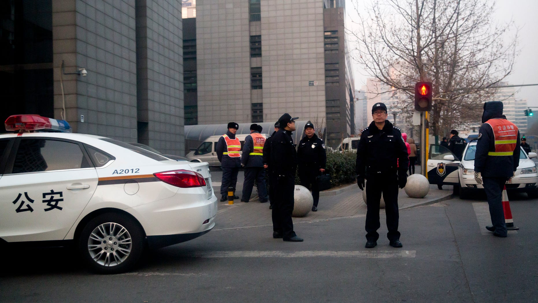 Chinese policemen stand guard as they condone off streets near the Haidian District Court, where Zhao Changqing, an activist of the New Citizens movement, was to stand trial in Beijing Thursday, Jan. 23, 2014. China's authorities and state media highlighted a prominent businessman's renunciation of ties to the grassroots social movement that he had financed and his alleged suggestion that the movement's founder Xu Zhiyong should confess to crimes on Thursday, while authorities are postponing several trials of members of the movement amid tight security. (AP Photo/Andy Wong)
