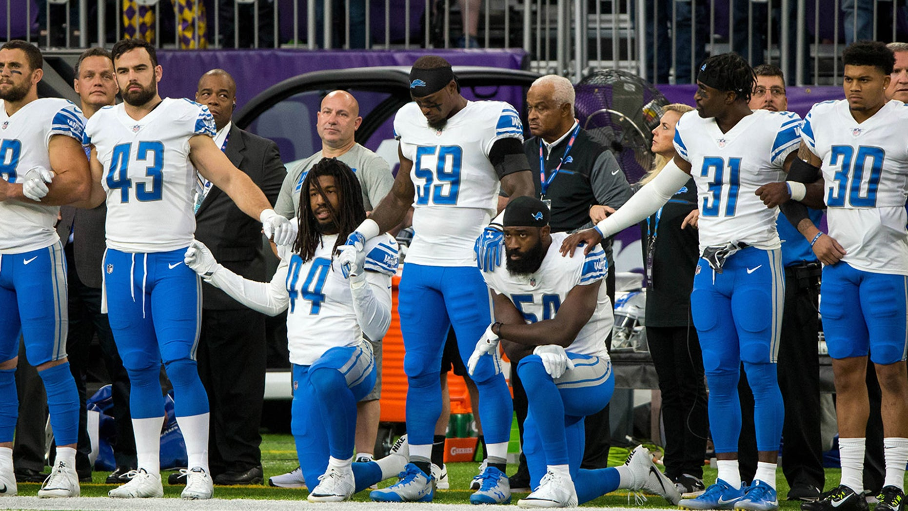 Detroit Lions players kneel while others stand during the national anthem before the game against the Minnesota Vikings.