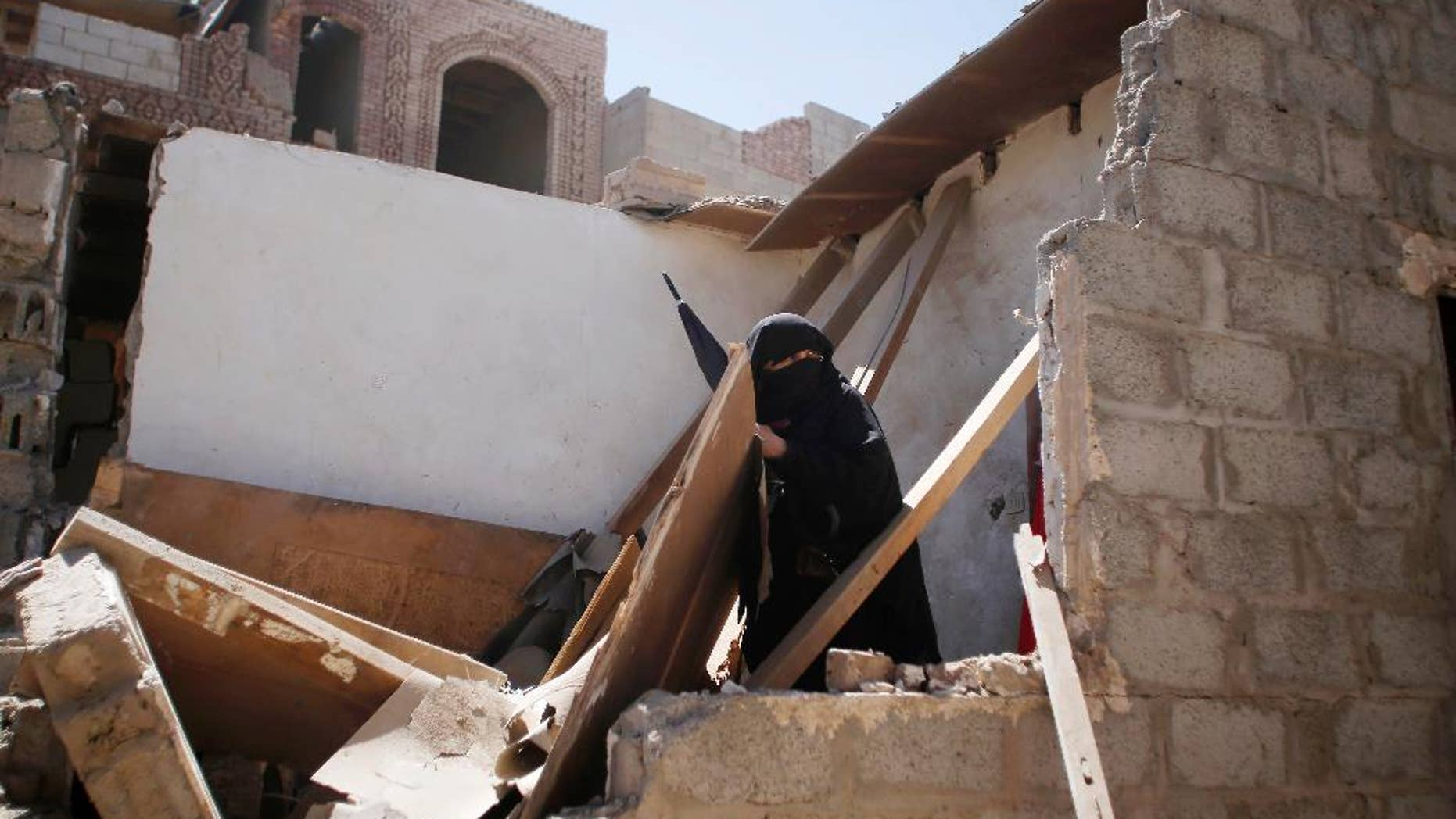 A woman stands on her house destroyed by Saudi-led airstrikes in Sanaa, Yemen, Friday, May 1, 2015. Saudi Arabia leads a coalition of mostly Sunni Arab countries conducting airstrikes against the rebels who have overrun the Yemeni capital, Sanaa, and forced the Western-backed president, Abed Rabbo Mansour Hadi, to flee the country. (AP Photo/Hani Mohammed)