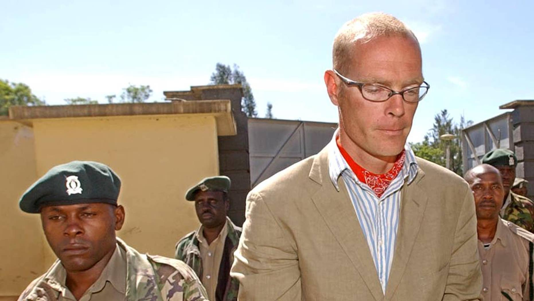 FILE---In this file photo of May 18, 2005, Thomas Patrick Gilbert Cholmondeley, right, grandson of the late Lord Delamare, is escorted to the Nakuru Court in Kenya. Cholmondeley, a descendant of British aristocrats who twice had been accused of murdering locals has died after cardiac arrest, a Kenya hospital official said Wednesday Aug. 17, 2016. (AP Photo/Sayyid Azim-file)
