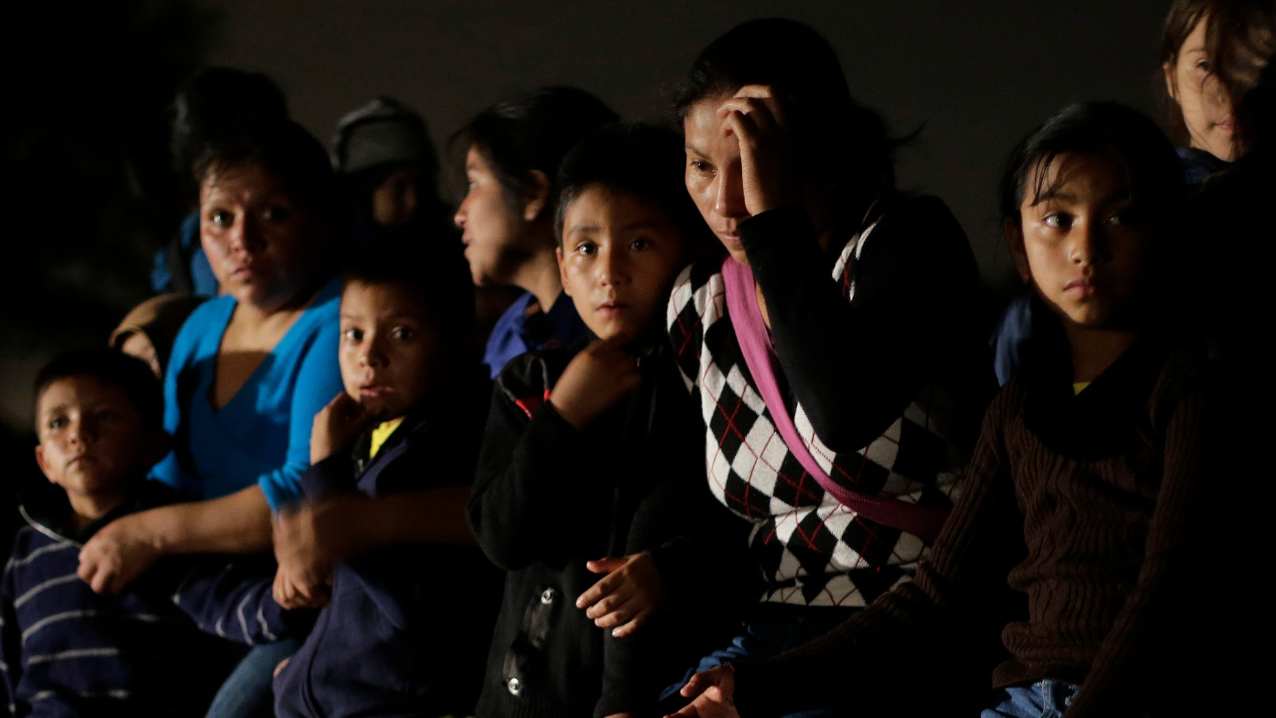 FILE - In this June 25, 2014 photo shows a group of  immigrants from Honduras and El Salvador who crossed the U.S.-Mexico border illegally are stopped in Granjeno, Texas. The influx at the border is largely families with children or by minors traveling alone. From October 2012 through the end of September 2013, the U.S. Border Patrol apprehended about 24,000 unaccompanied children. But between October and the end of June 2014, the number shot up to 57,000. Secretary of Homeland Security Jeh Johnson testified recently that the number is accelerating so fast that it could reach 90,000 by the end of September. Most of them are coming from El Salvador, Honduras and Guatemala. (AP Photo/Eric Gay, File)