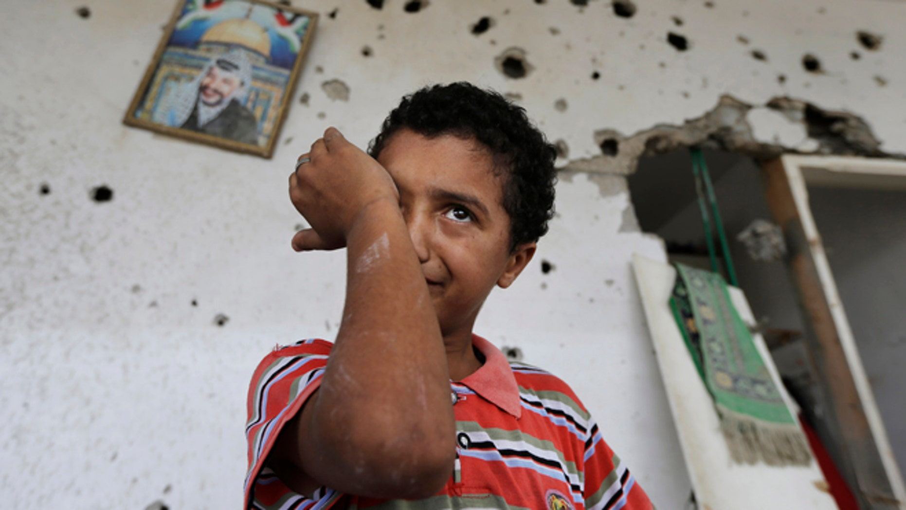 Backdropped by a picture of late Palestinian leader Yasser Arafat, Palestinian Anas Shabat, 10, weeps as he inspects damages upon returning to his family house, destroyed by Israeli strikes in the town of Beit Hanoun, northern Gaza Strip, Tuesday, Aug. 5, 2014. Israel and Hamas began observing a temporary cease-fire on Tuesday that sets the stage for talks in Egypt on a broader deal on the Gaza Strip, including a sustainable truce and the rebuilding of the battered, blockaded coastal territory. (AP Photo/Lefteris Pitarakis)
