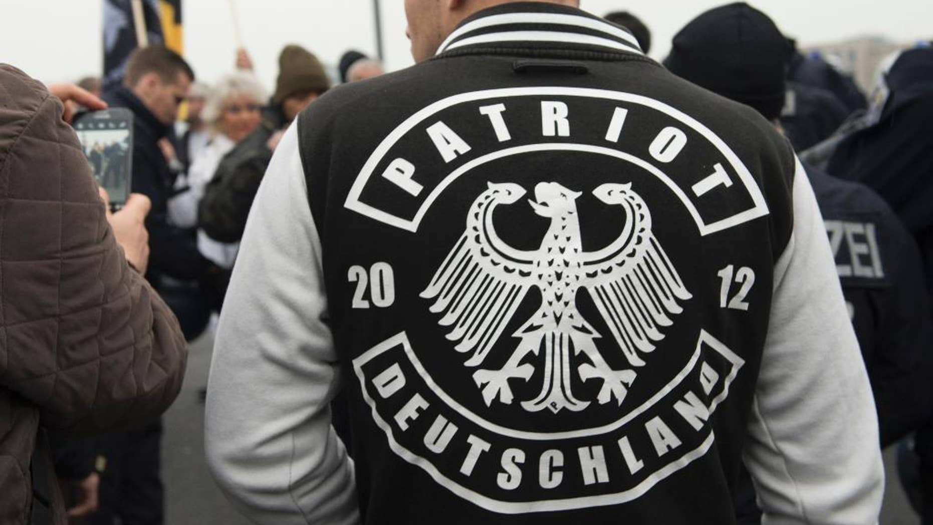 """A demonstrator wears a jacket with the writing """"Patriot Deutschland"""" (lt. Germany Patriot) during the fourth demonstration of the right-wing populist alliance 'Wir fuer Deutschland' in Berlin, Germany, Saturday,  Nov. 5, 2016. (Paul Zinken/dpa via AP)"""