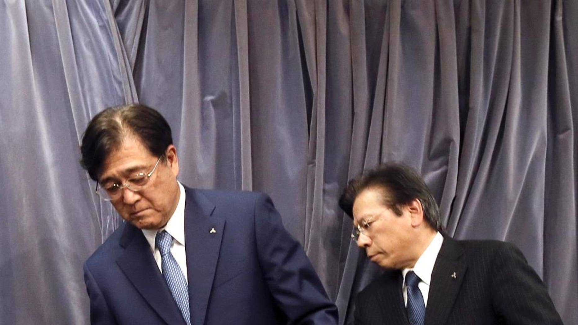 FILE - In this May 11, 2016 photo, Mitsubishi Motors Corp. Chairman and CEO Osamu Masuko, left, and President Tetsuro Aikawa prepare for their press conference in Tokyo.  Mitsubishi Motors Corp., which recently acknowledged it inflated mileage for its models, is forecasting a 145 billion yen ($1.4 billion) loss for the fiscal year through March 2017. The Japanese automaker said Wednesday, June 22,  vehicle sales will drop around the world, especially in Japan, where it expects a 41 percent plunge. The projected loss is a reversal from the 72.6 billion yen profit for the fiscal year ended March.   (AP Photo/Eugene Hoshiko, File)