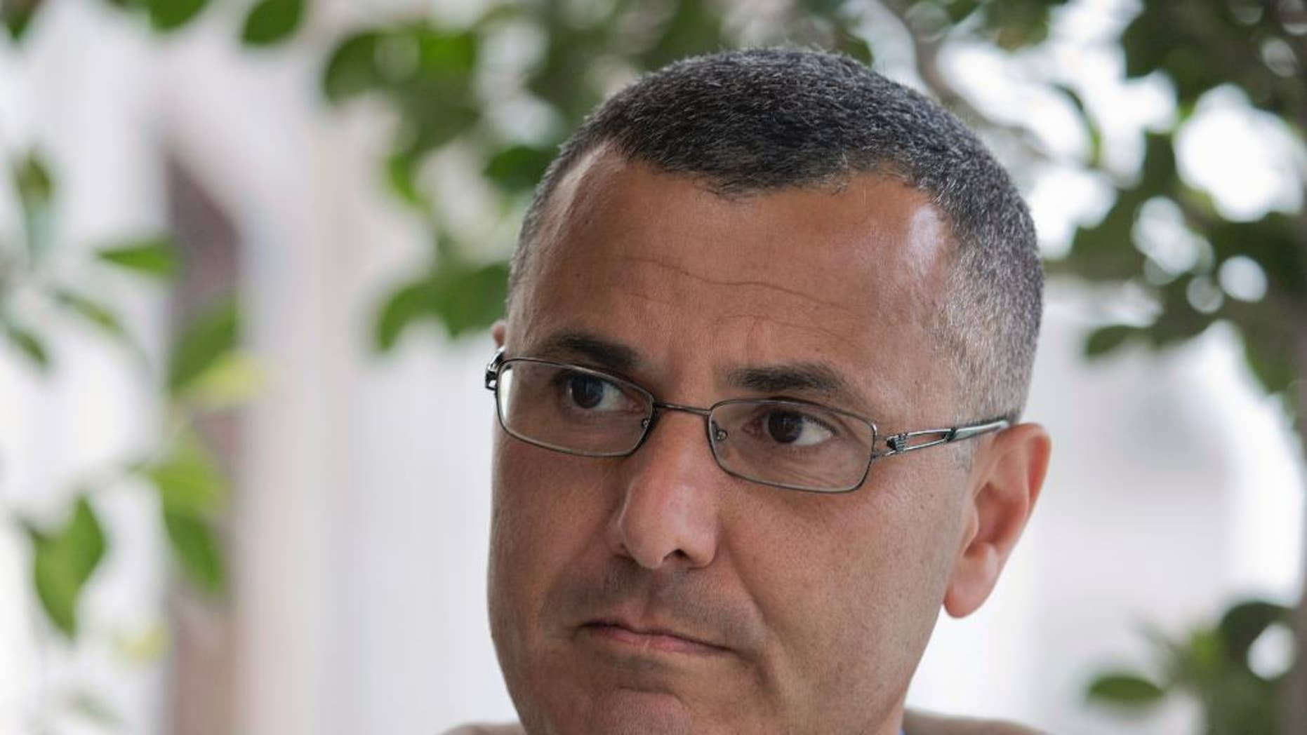 Omar Barghouti listens during an interview with the Associated Press in the West Bank city of Ramallah, Tuesday, May 10, 2016. Barghouti, a Qatari-born Palestinian who is married to an Israeli woman and leader of the international boycott movement against Israel, on Tuesday accused Israeli authorities of imposing a travel ban on him as retribution for his political activities. (AP Photo/Nasser Nasser)