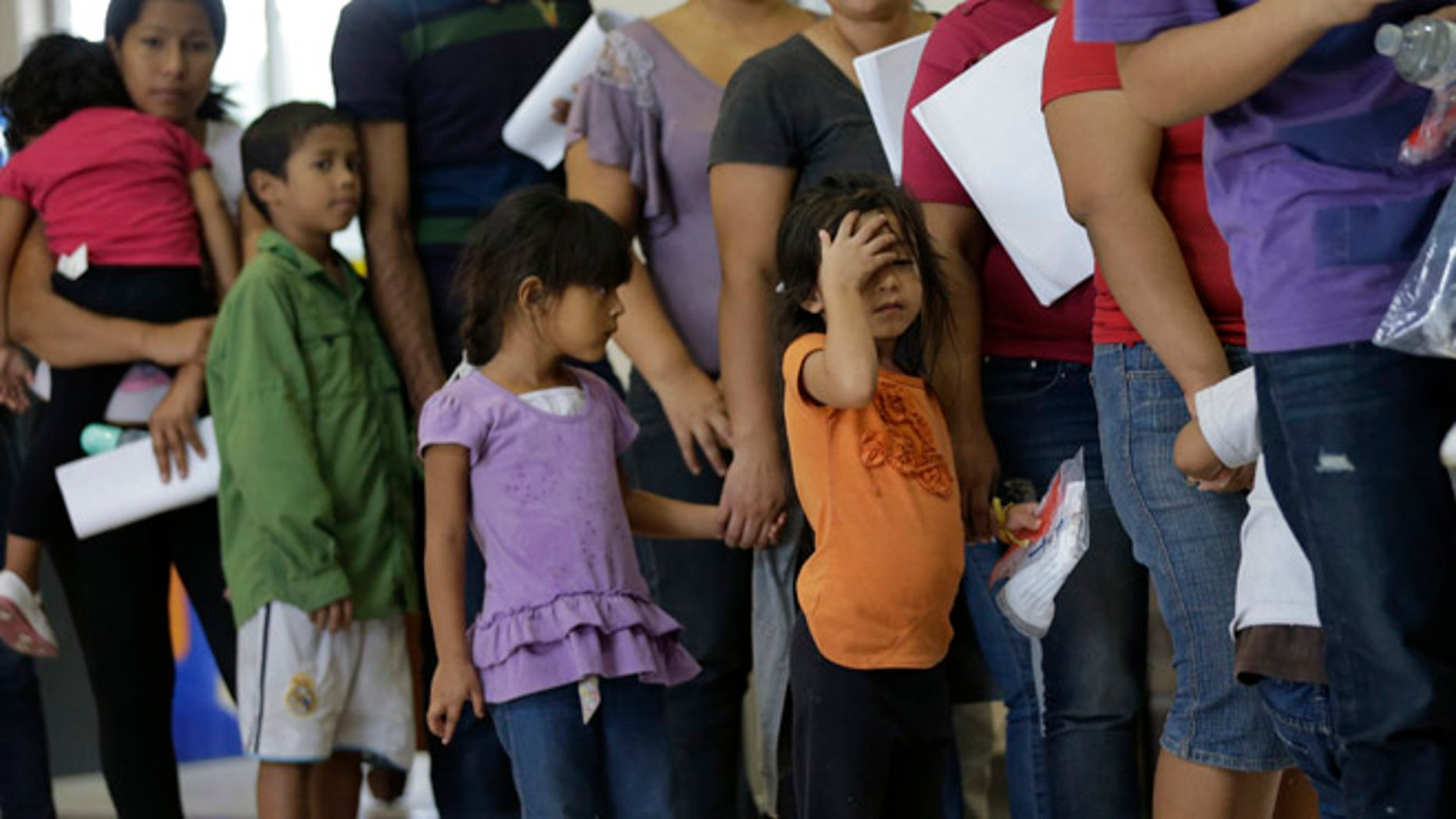 FILE - In this June 20, 2014 file photo, immigrants who entered the U.S. illegally stand in line for tickets at the bus station after they were released from a U.S. Customs and Border Protection processing facility in McAllen, Texas. Tackling what he has called a humanitarian crisis, President Barack Obama on Tuesday, July 8, 2014 asked Congress for $3.7 billion to cope with a tide of minors from Central America who are illegally crossing the U.S. border, straining immigration resources and causing a political firestorm in Washington.  (AP Photo/Eric Gay, File)