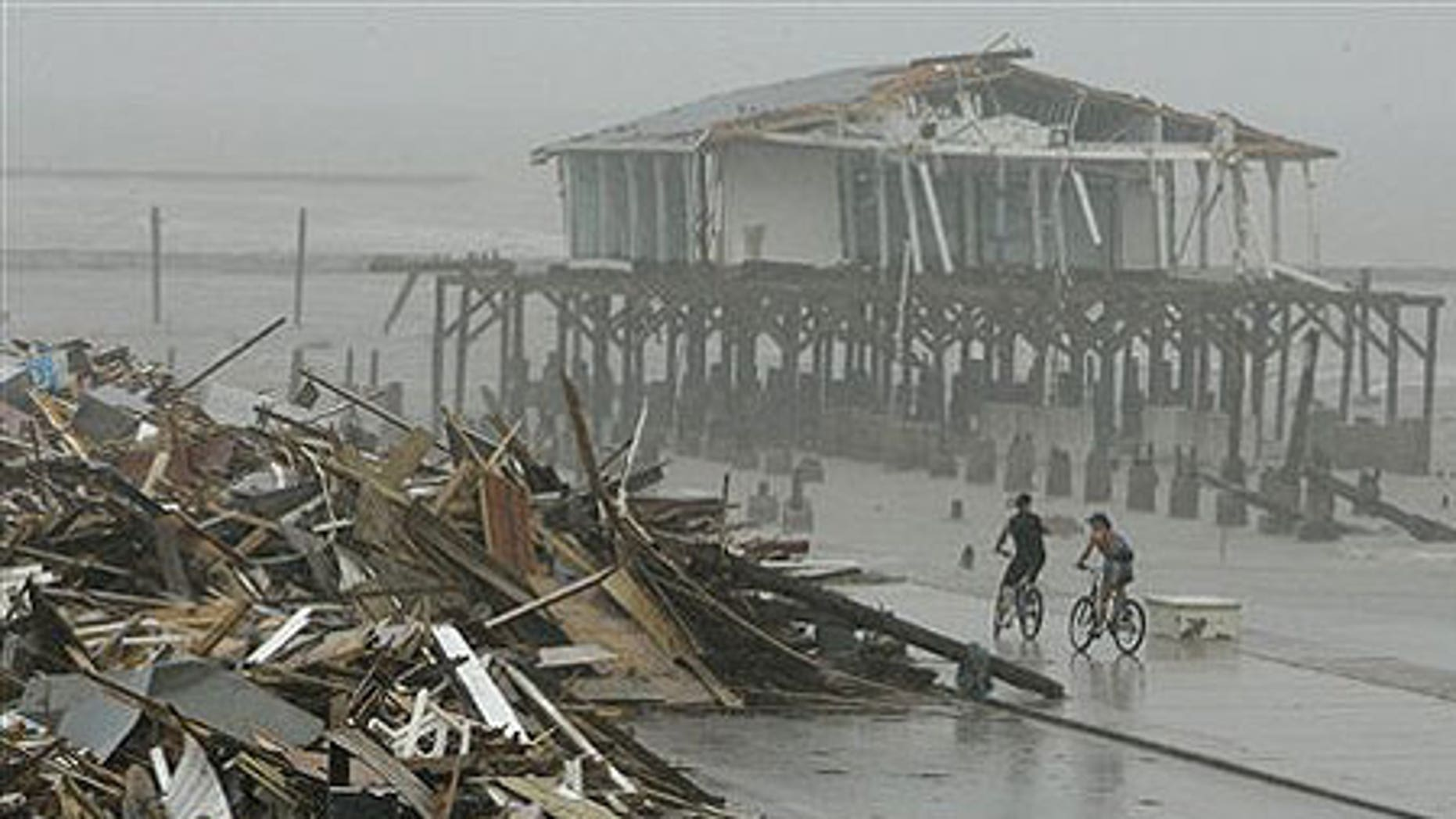 Sept. 14: Cyclists ride past debris piled up on the seawall road after Hurricane Ike hit the Texas coast.