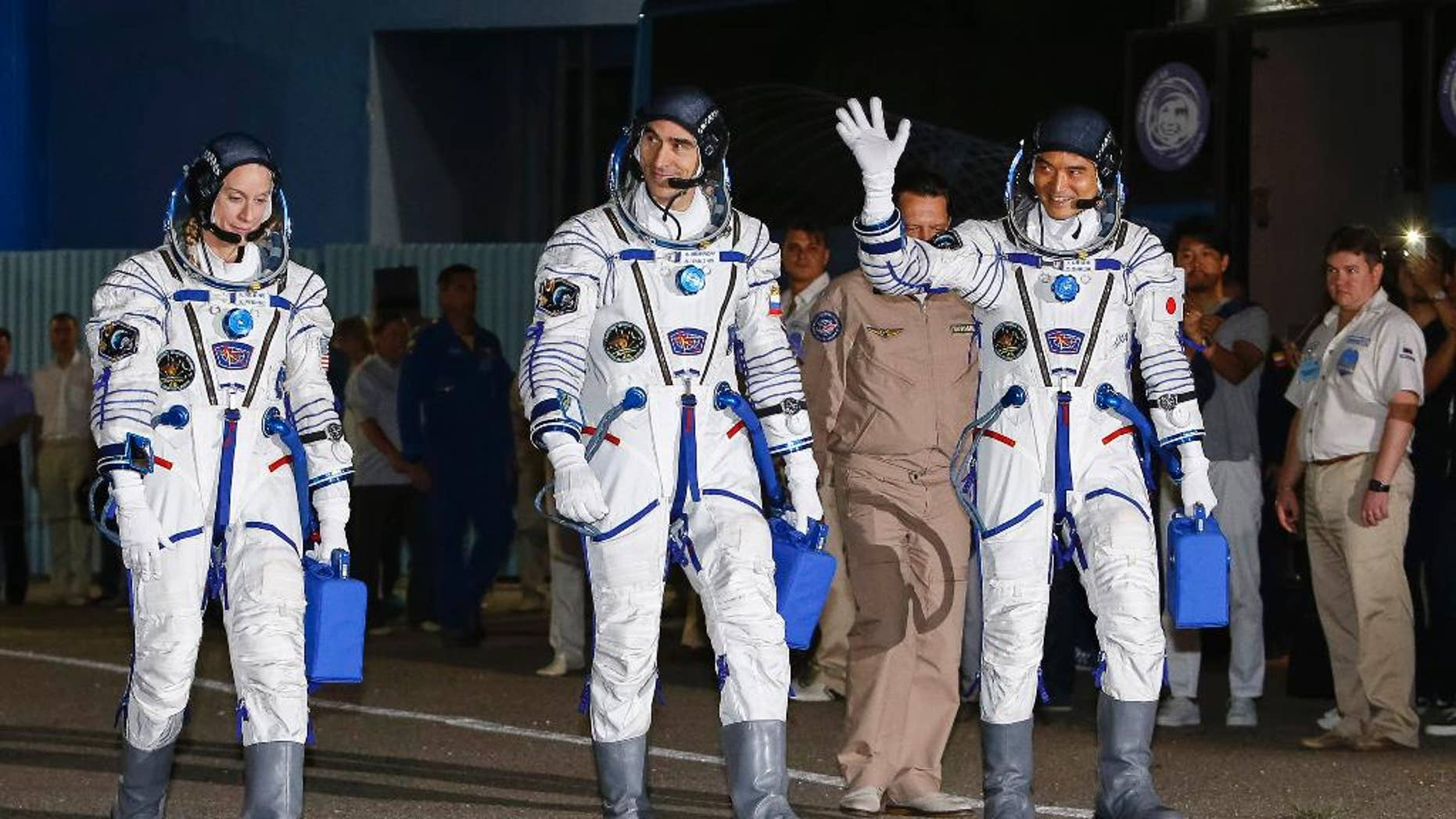 July 7, 2016: U.S. astronaut Kate Rubins, left, Russian cosmonaut Anatoly Ivanishin, centre, and Japanese astronaut Takuya Onishi, members of the main crew of the expedition to the International Space Station (ISS), walk to report to members of the State Committee prior to the launch of Soyuz MS space ship at the Russian leased Baikonur cosmodrome, Kazakhstan.