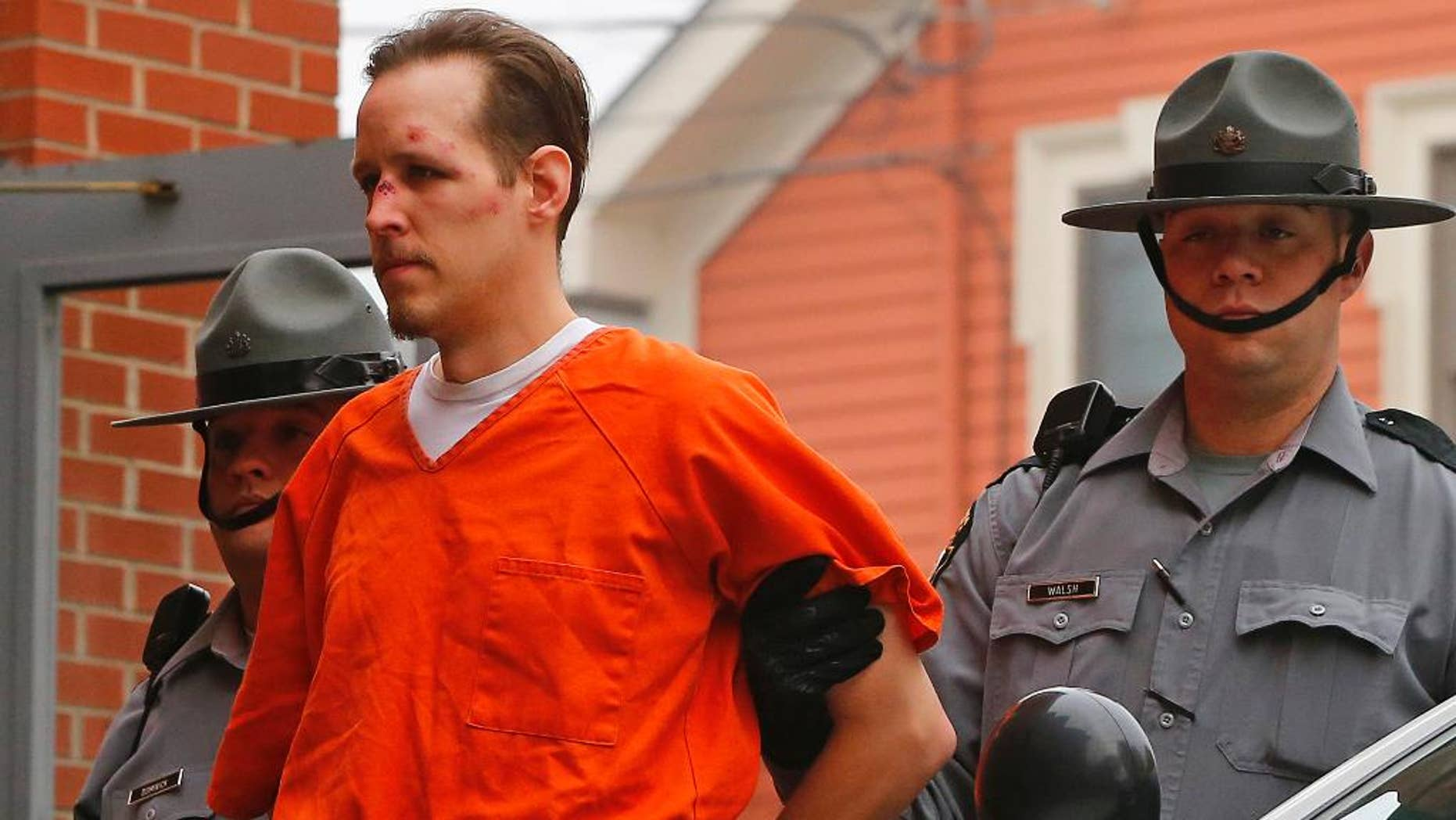 FILE - In this Oct. 31, 2014 file photo Eric Frein is escorted by police into the Pike County Courthouse for his arraignment in Milford, Pa. Frein a survivalist who eluded capture for 48 days after allegedly killing a trooper in a 2014 ambush says police were about a football field away from him at one point during the manhunt. Authorities say they found Eric Frein's journal at the airplane hangar where he was hiding out until his arrest. A trooper testified about the journal at Frein's capital murder trial Wednesday, April 12, 2017.   (AP Photo/Rich Schultz, File)