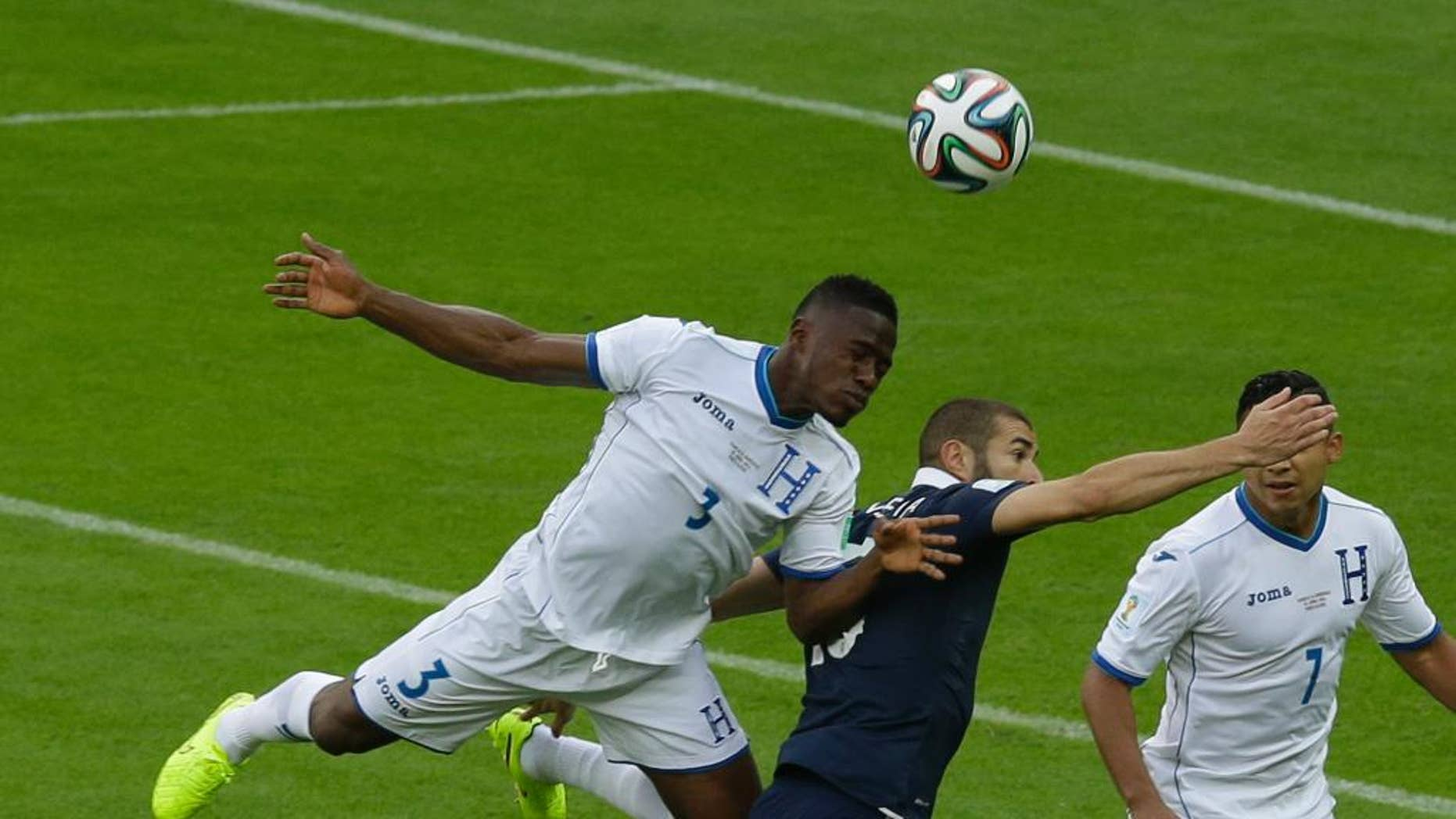 Honduras' Maynor Figueroa, left, and France's Karim Benzema challenge for the ball during the group E World Cup soccer match between France and Honduras at the Estadio Beira-Rio in Porto Alegre, Brazil, Sunday, June 15, 2014. (AP Photo/Andrew Medichini)