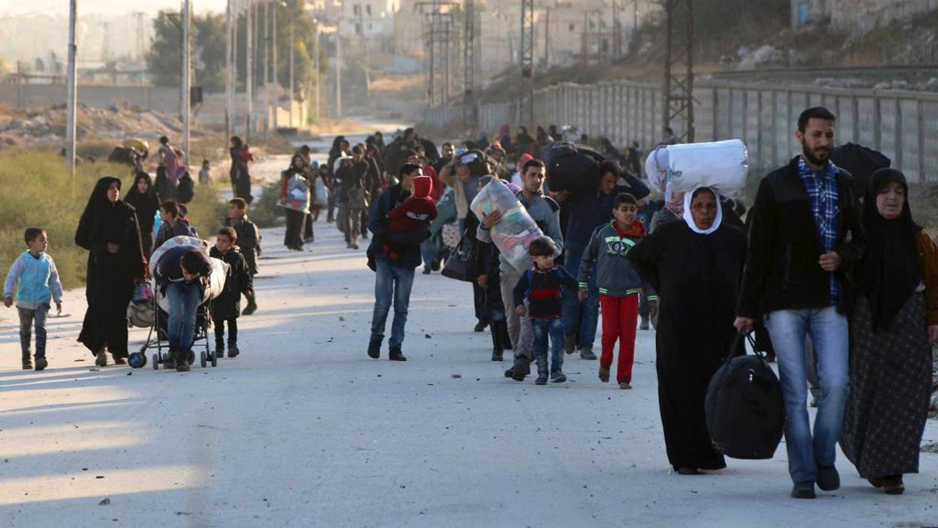 FILE - In this Sunday, Nov. 27, 2016 file photo provided by the Rumaf, a Syrian Kurdish activist group, which has been authenticated based on its contents and other AP reporting, shows people fleeing rebel-held eastern neighborhoods of Aleppo into the Sheikh Maqsoud area that is controlled by Kurdish fighters, Syria. The U.N. humanitarian aid agency said Friday an estimated 31,500 have been displaced from the government advances into the rebel-held enclave since this weekend, in one of the most dramatic shifts in the conflict now in its sixth year. (The Rumaf via AP, File)