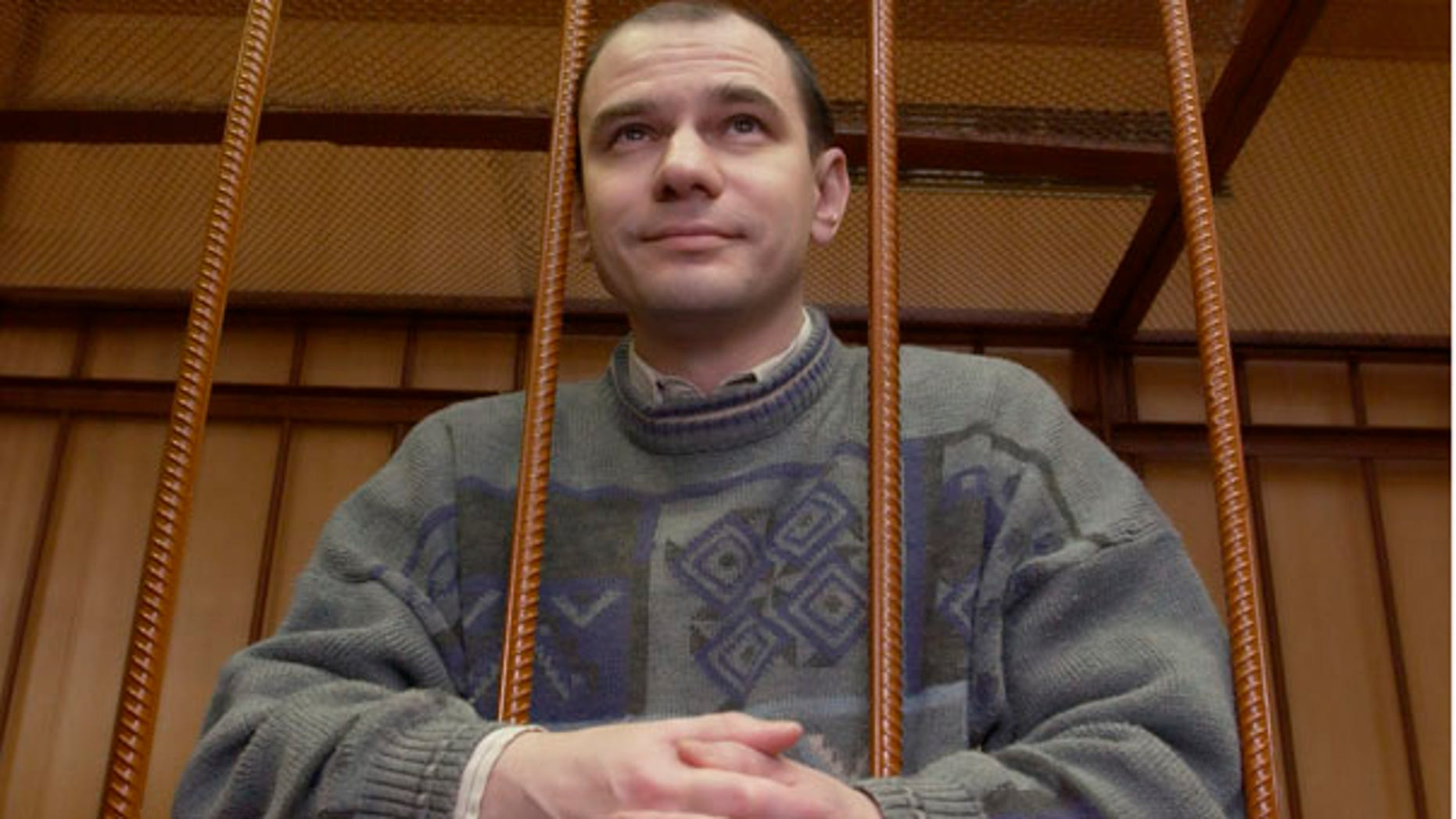 FILE: Russian arms control researcher Igor Sutyagin stands behind bars as he's sentenced to 15 years in prison for spying on April 7, 2004 in a Moscow courtroom.