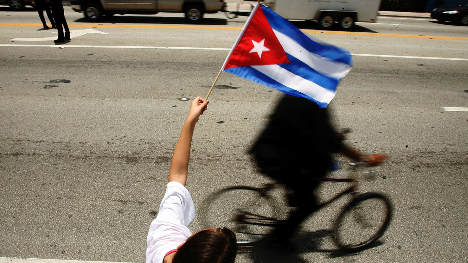 MIAMI - AUGUST 1:  Ana Maria Acevedo, 10, waves a Cuban flag along the famous Calle Ocho in the Little Havana neighborhood August 1, 2006 in Miami, Florida. Acevedo immigrated to the U.S. from Cuba in 2000. Cuban Americans were celebrating the news that Fidel Castro had turned over power to his younger brother, Raul Castro, while he undergoes medical treatment for intestinal bleeding.  (Photo by Chip Somodevilla/Getty Images)