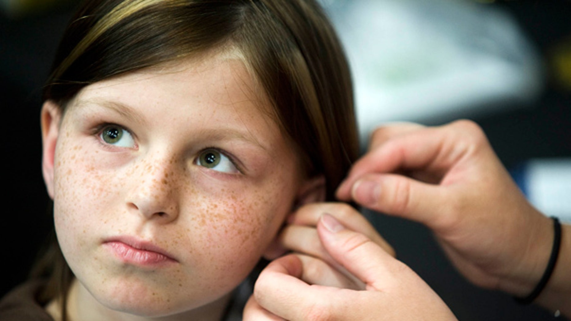 This May 2010 photo shows Zahra Baker, 10, getting a hearing aid at an event at Charlotte Motor Speedway.
