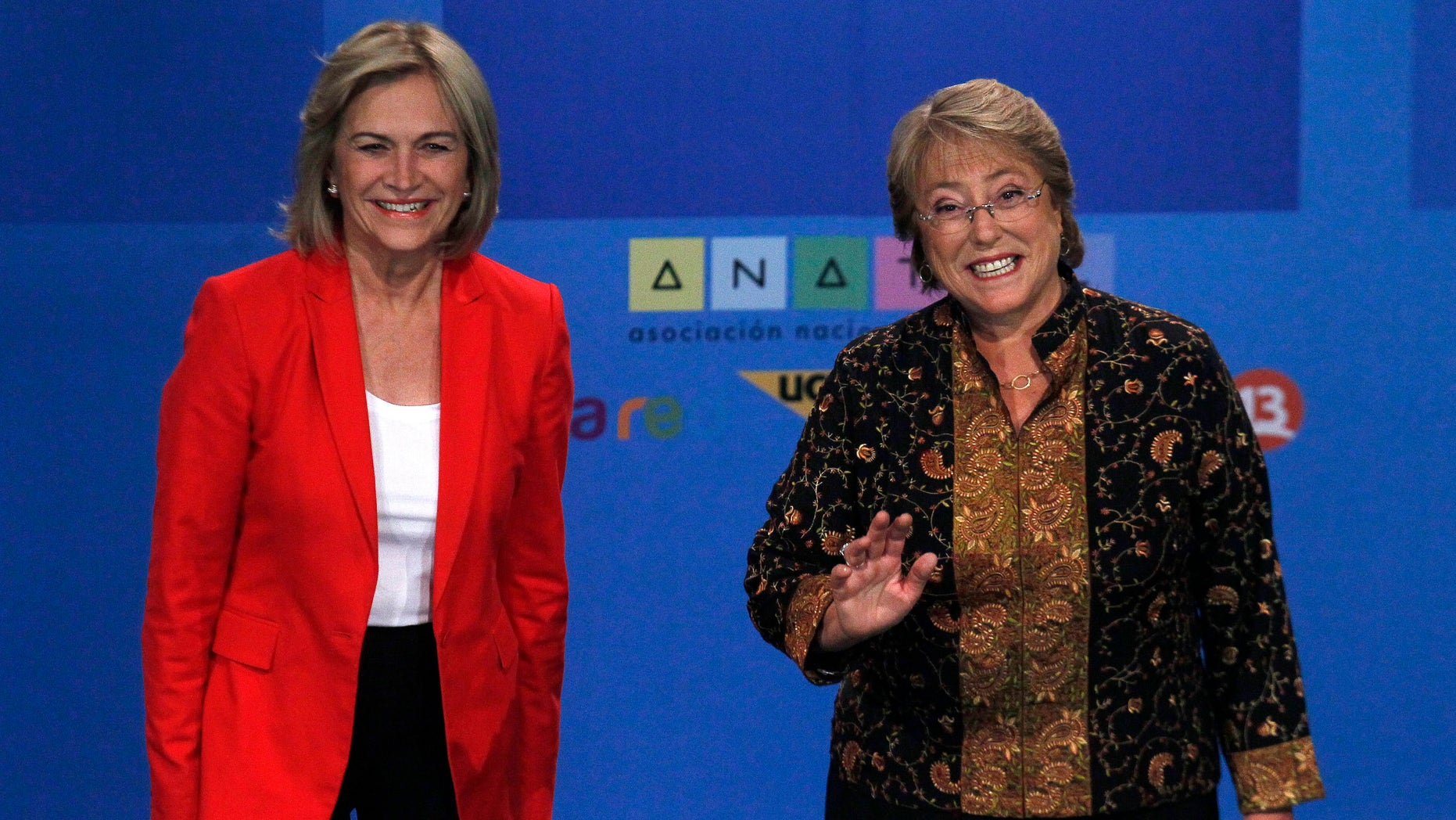 In this Tuesday, Dec. 10, 2013 photo, Chile's presidential candidate Michelle Bachelet, right, and rival Evelyn Matthei, smile for photographers before their television debate in Santiago, Chile. Bachelet and Matthei were childhood friends, but found themselves on opposite sides of the deep political divide after Chile's bloody 1973 military coup. Bachelet, who became Chile's first women president from 2006-2010, is now expected to retake the presidency in the Dec. 15 run-off election. (AP Photo/ Luis Hidalgo)