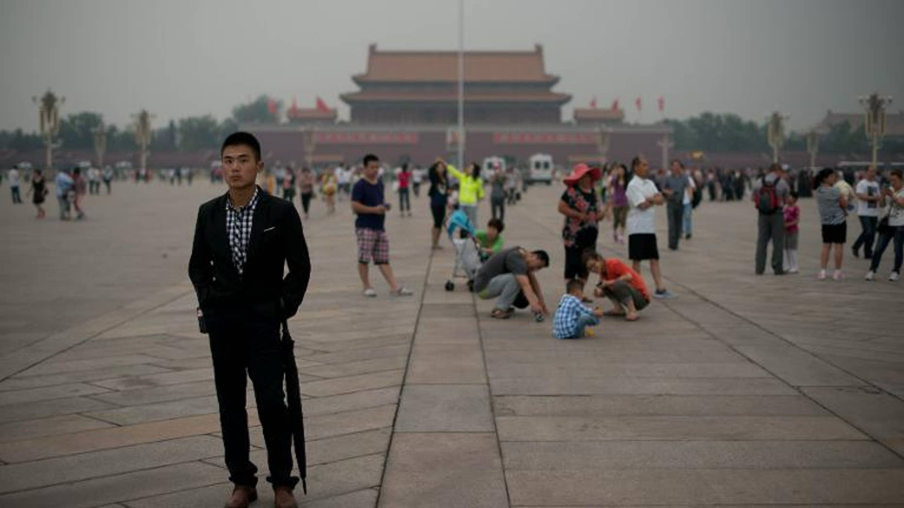 A plain-clothes policeman (L) at Tiananmen square in Beijing on June 4, 2013.