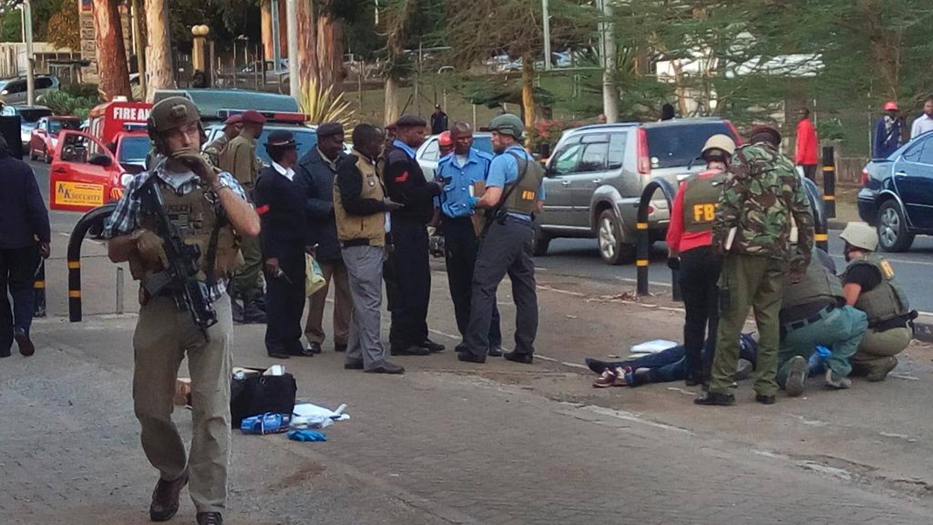 Unidentified U.S. Embassy personnel and Kenyan security forces stand near to the body, right, of a man who was killed outside the U.S. Embassy in Nairobi, Kenya Thursday, Oct. 27, 2016. A Kenyan police official said the man was shot dead after stabbing a policeman guarding the perimeter wall of the U.S. Embassy in Nairobi. (AP Photo/Moses Muoki)