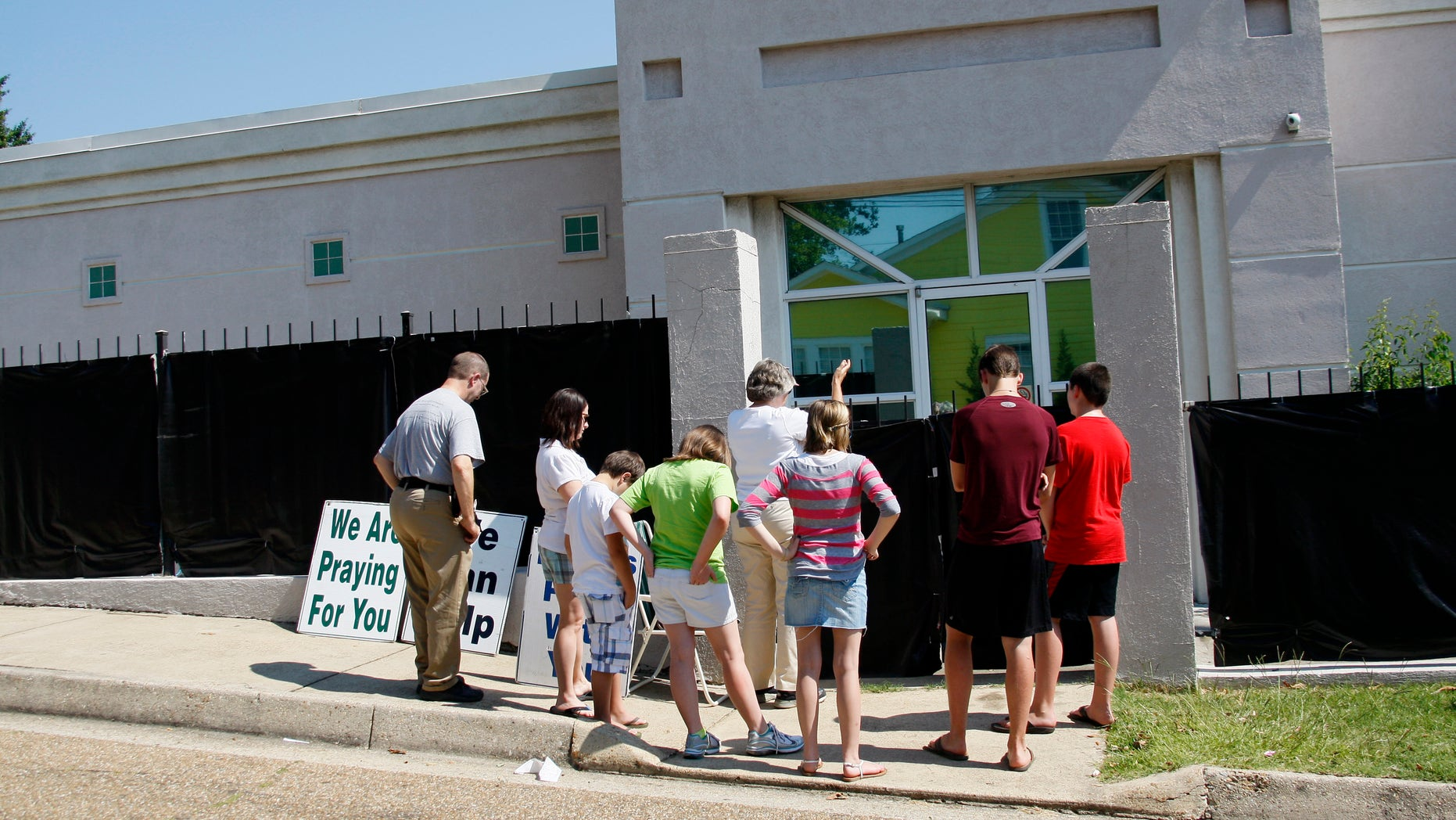 """June 27, 2012: In this photograph, anti-abortion advocates stand outside Mississippi's only abortion clinic, singing and praying for their patients, and """"counseling"""" them to reject abortion."""
