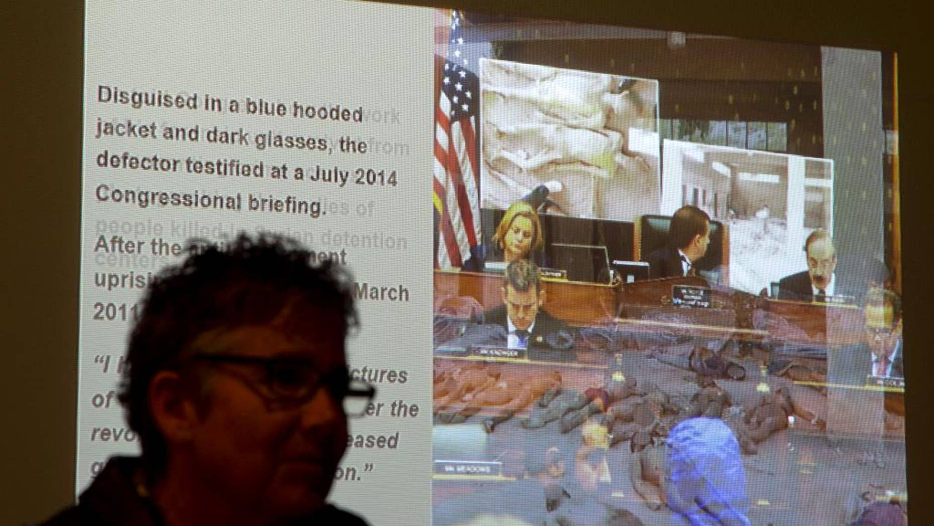 """FILE - In this Oct. 15, 2014, file photo, US Holocaust Memorial Museum visitor Marianne Kast, from Fresno, Calif., watches a slide show presentation of images of emaciated and mangled bodies from recent history in Syria in an exhibit entitled """"Genocide: The Threat Continues,"""" at the museum in Washington. Almost helpless in the U.N. Security Council to take strong action on Syria, the United States and other states are hoping to shame its government by sponsoring a graphic photo exhibit of detainees who've died in President Bashar Assad's prisons since the country's conflict began. Fifteen countries will join the opposition Syrian National Coalition on Tuesday, March 10, 2015, at United Nations headquarters to launch the exhibit of portraits showing signs of torture and starvation and to call for an end to the crisis that enters its fifth year this month. (AP Photo/Manuel Balce Ceneta, File)"""