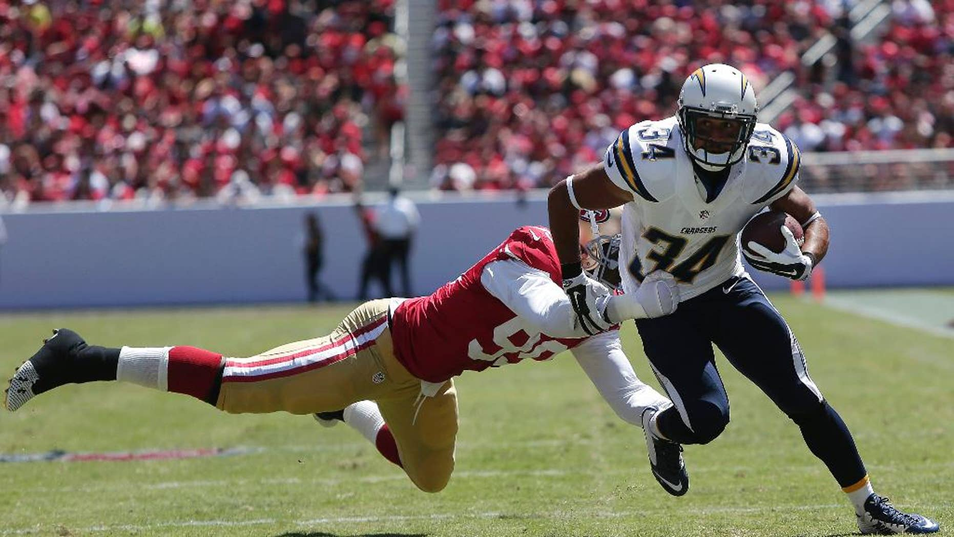 San Diego Chargers running back Donald Brown (34) runs from San Francisco 49ers linebacker Aldon Smith during the first quarter of an NFL preseason football game in Santa Clara, Calif., Sunday, Aug. 24, 2014. (AP Photo/Marcio Jose Sanchez)