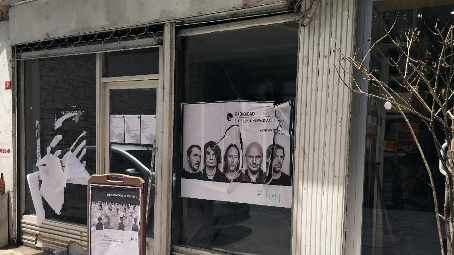 A ripped up poster advertising the streaming event of Radiohead's new album, at a record shop, in Istanbul, Saturday, June 18, 2016. Turkish media report a mob of 20 assailants carrying sticks and bottles attacked Radiohead fans who had gathered at a record store in Istanbul to listen to the band's new album. The private Dogan news agency reported Saturday that one person was wounded in the incident Friday at the Velvet Indieground record shop. (AP Photo/Dominique Soguel)