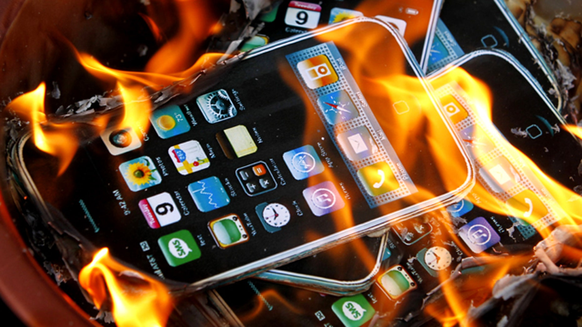 May 25, 2010: Cardboard cutouts resembling iPhones are in flames after they were set on fire by labor activists near the Foxconn office in Hong Kong, following a string of deaths at the world's largest contract maker of electronics.