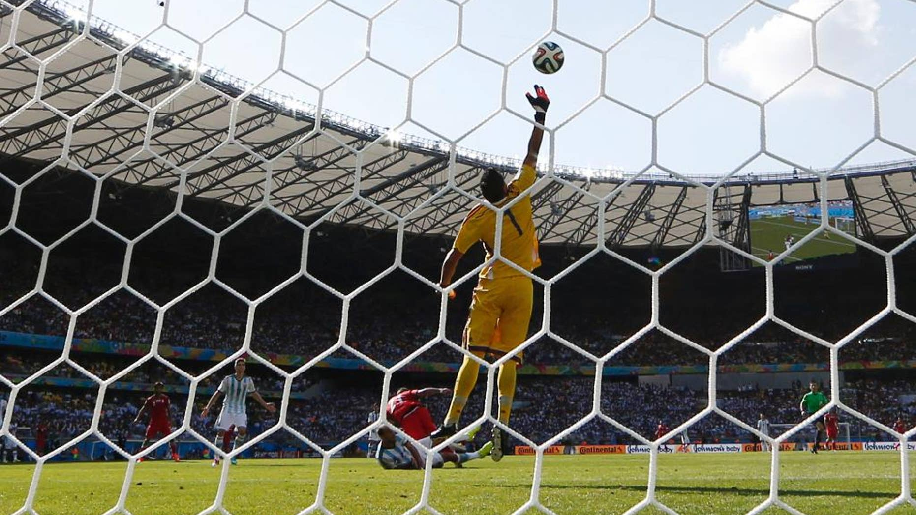 Argentina's goalkeeper Sergio Romero deflects a header by Iran's Ashkan Dejagah over the goal during the group F World Cup soccer match between Argentina and Iran at the Mineirao Stadium in Belo Horizonte, Brazil, Saturday, June 21, 2014. (AP Photo/Fernando Vergara)