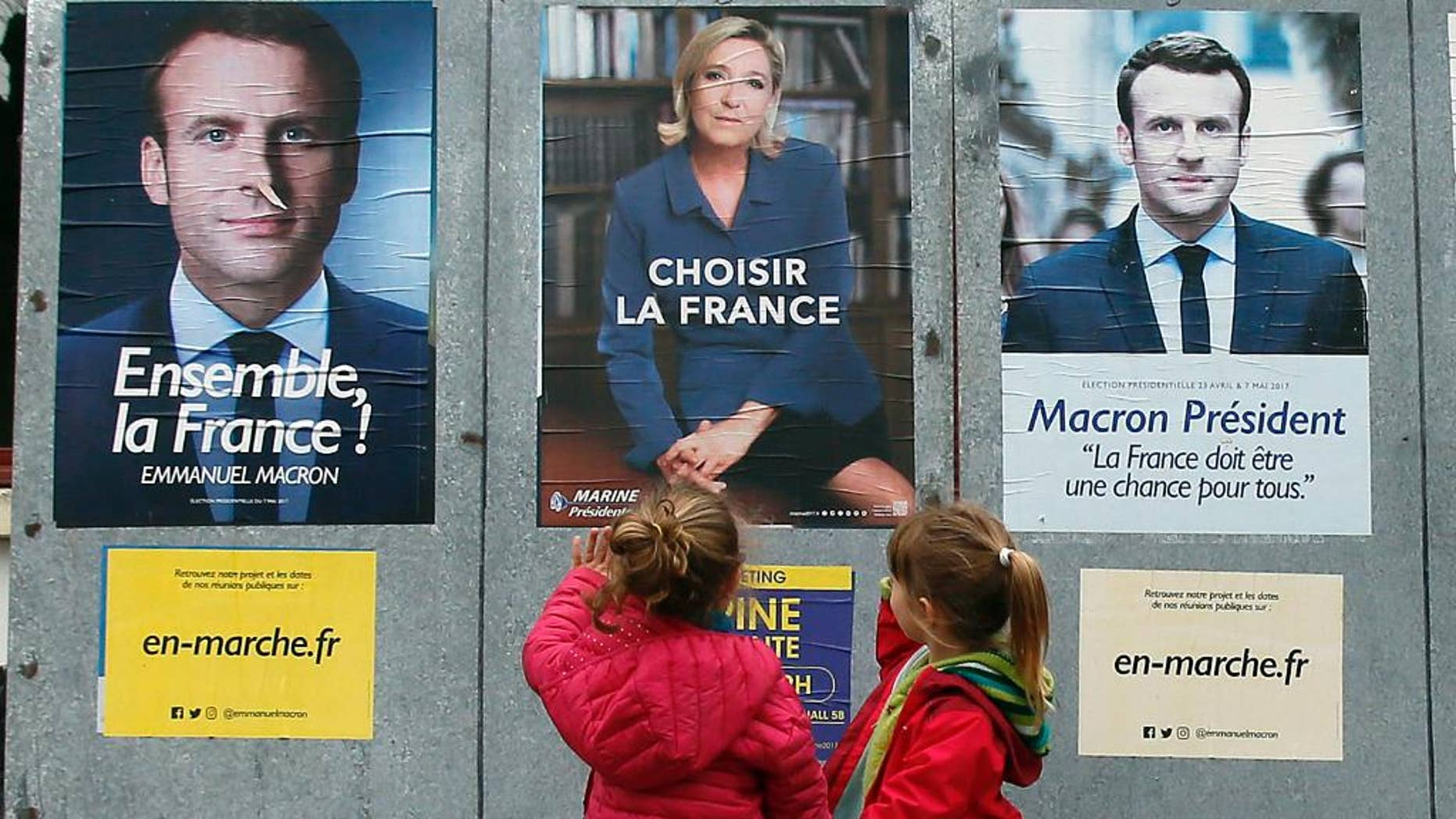 Children walk past election campaign posters for French centrist presidential candidate Emmanuel Macron and far-right candidate Marine Le Pen, in Osses, southwestern France, Friday May 5, 2017. France will vote on Sunday May 7 in the second round of the presidential election. (AP Photo/Bob Edme)