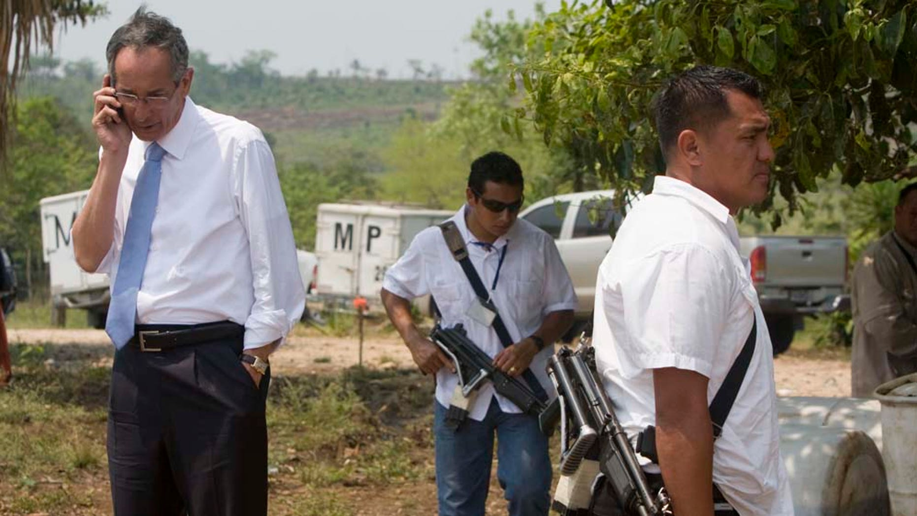 Guatemala's President Alvaro Colom, left, talks on a mobile phone while inspecting the site of a massacre at a local ranch in the hamlet Caserio La Bomba, in La Libertad, northern Guatemala, Monday, May 16, 2011. Assailants killed Sunday at least 29 people, including two children and two women, decapitating most of the victims on the ranch near the Mexico border, according to National Civil Police spokesman Donald Gonzalez. (AP Photo/Moises Castillo)