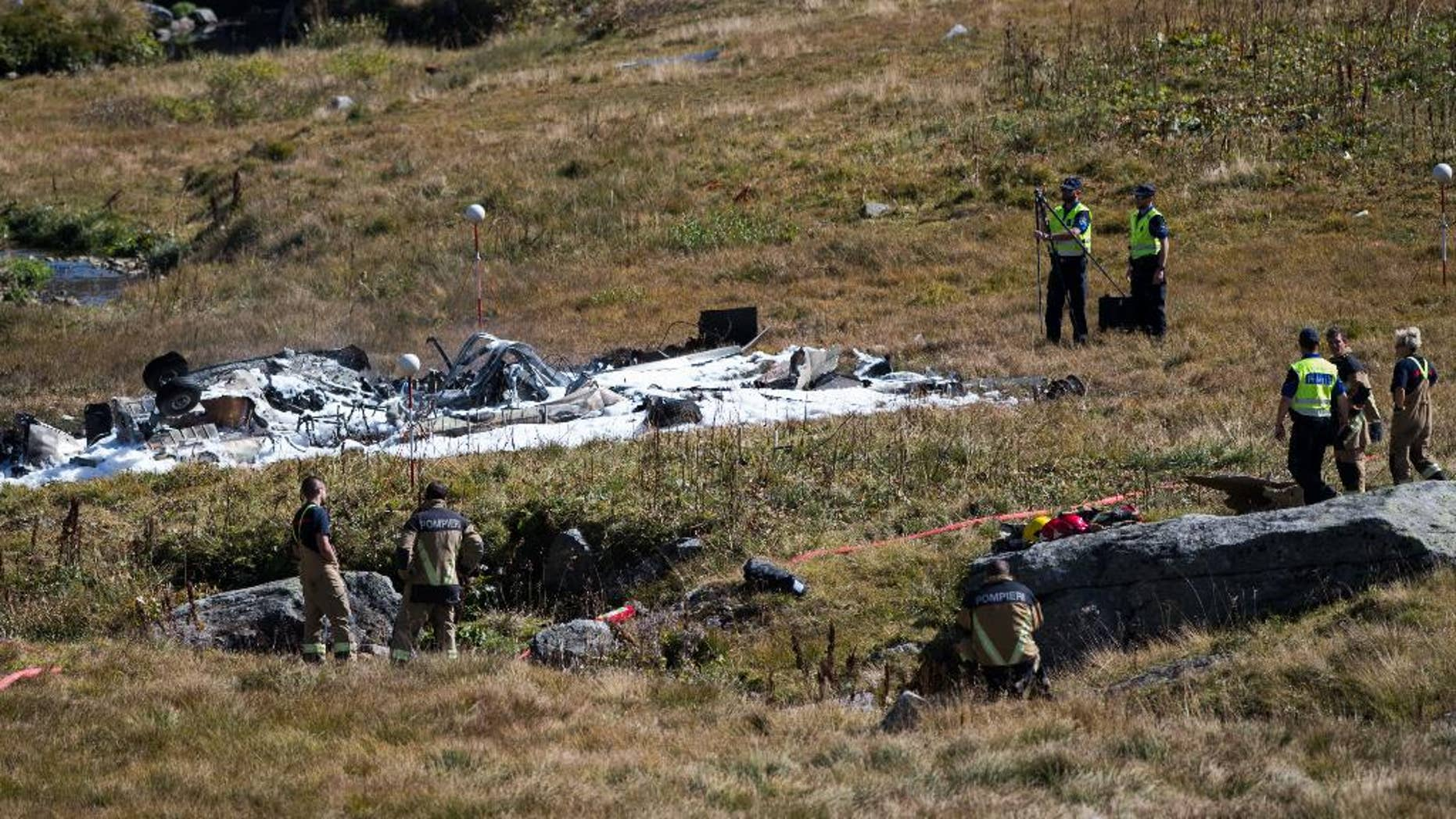 Rescue workers stand arround the debris oft the crashed Swiss army helicopter in the Alps near the Gotthard mountain pass in Airolo, southern Switzerland, Wednesday, Sept. 28 2016. The head of Switzerland's air force says one of its Super Puma helicopters has crashed, killing two pilots on board and injuring a flight assistant.  (Samuel Golay/Ti-Press/Keystone via AP)
