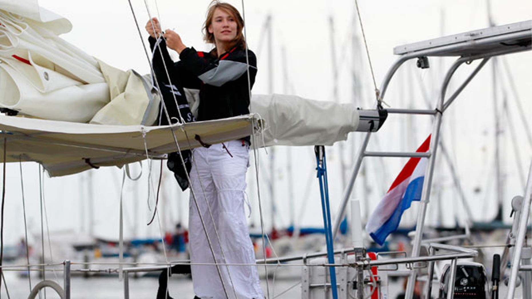 In this file photo dated Wednesday, Aug. 4, 2010 Laura Dekker hoists a flag of The Sea Shepherd Conservation Society on her boat in the harbor of Den Osse, southwest Netherlands. The 14-year-old Dutch girl will try to become the youngest person to sail solo around the world when she sets off from Portugal on Saturday Aug. 21, 2010. Laura Dekker's ambition of completing the yearlong trip has fueled a global debate over the wisdom of allowing young sailors to take on the tremendous risks of sailing the high seas alone.